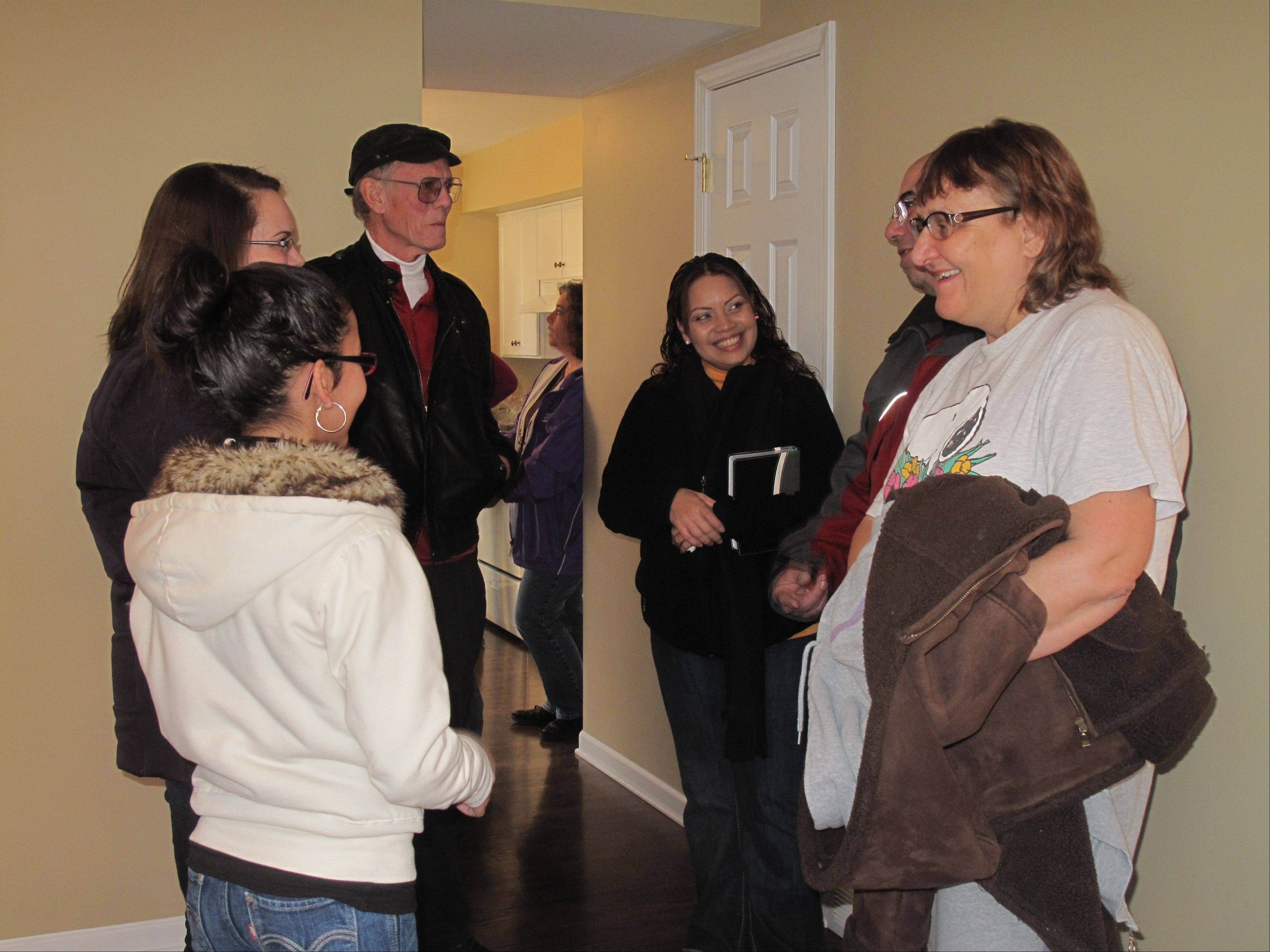 Enid Vargas, center, talks with Fox Valley Habitat for Humanity staff members and previous home recipients Saturday during a dedication ceremony at her new townhouse in North Aurora.