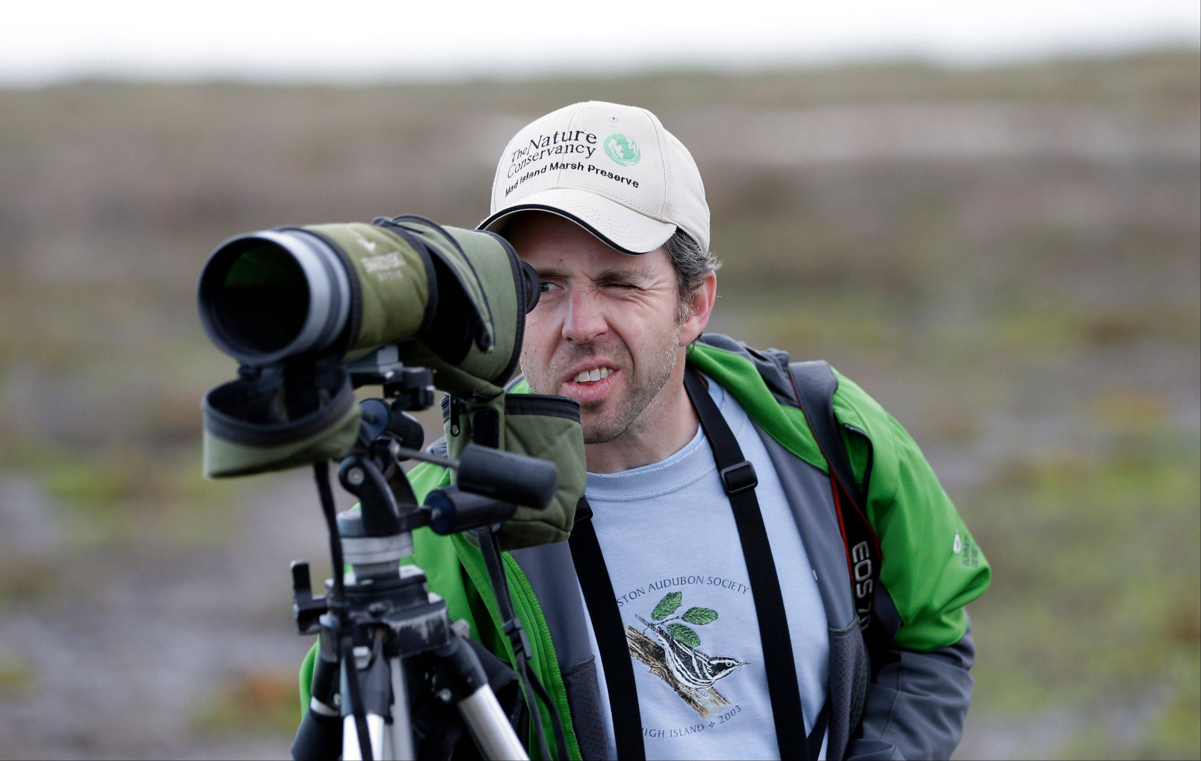 Rich Kostecke, a bird expert and associate director of conservation, research and planning at the Nature Conservancy in Texas, looks through his spotting scope Monday during an annual 24-hour Christmastime ritual to count birds along the Texas Gulf Coast in Mad Island, Texas.