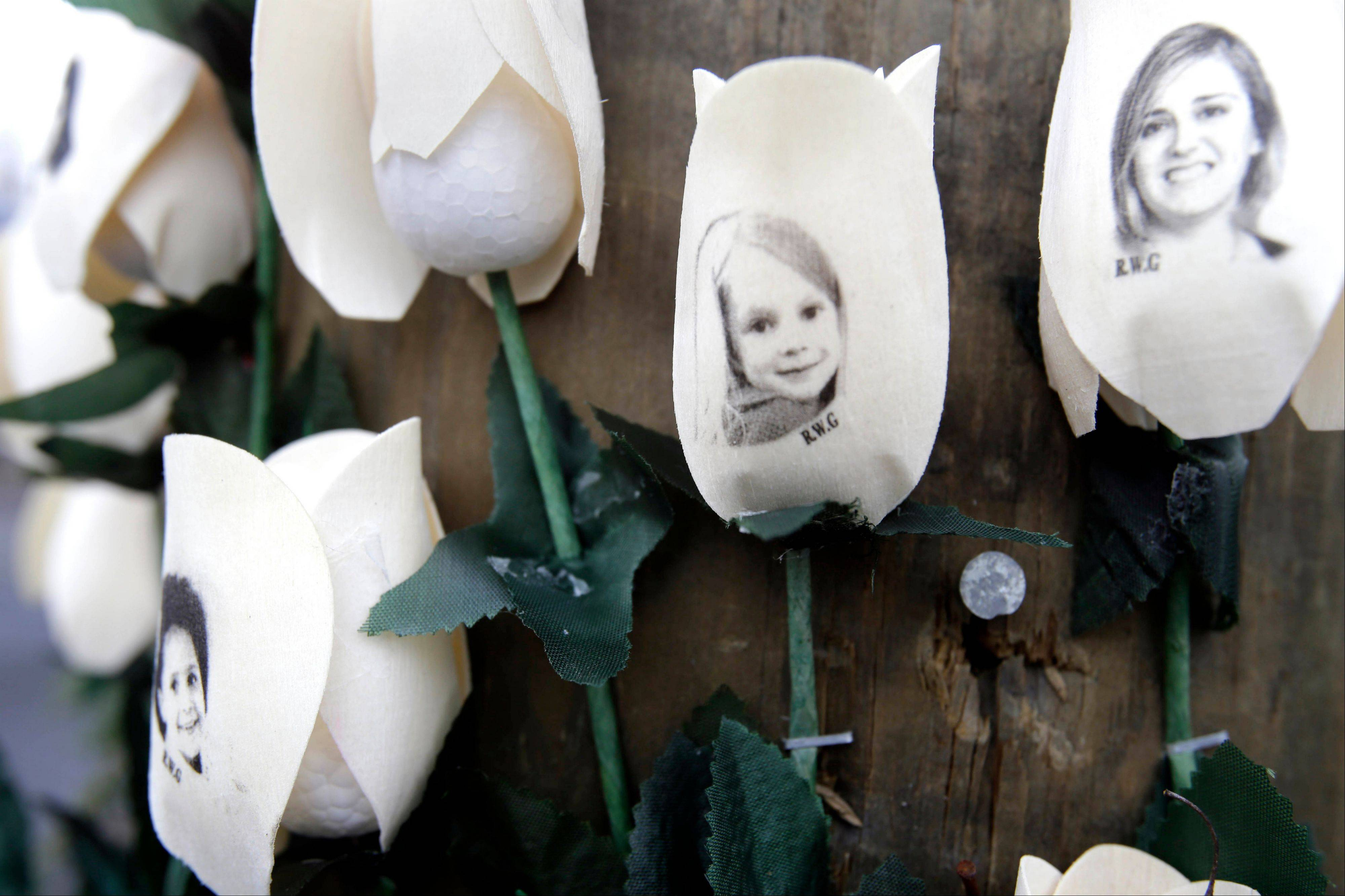 Photos showing victims in the shootings at Sandy Hook Elementary School are imprinted on fake roses at a memorial Saturday in the Sandy Hook village of Newtown, Conn.