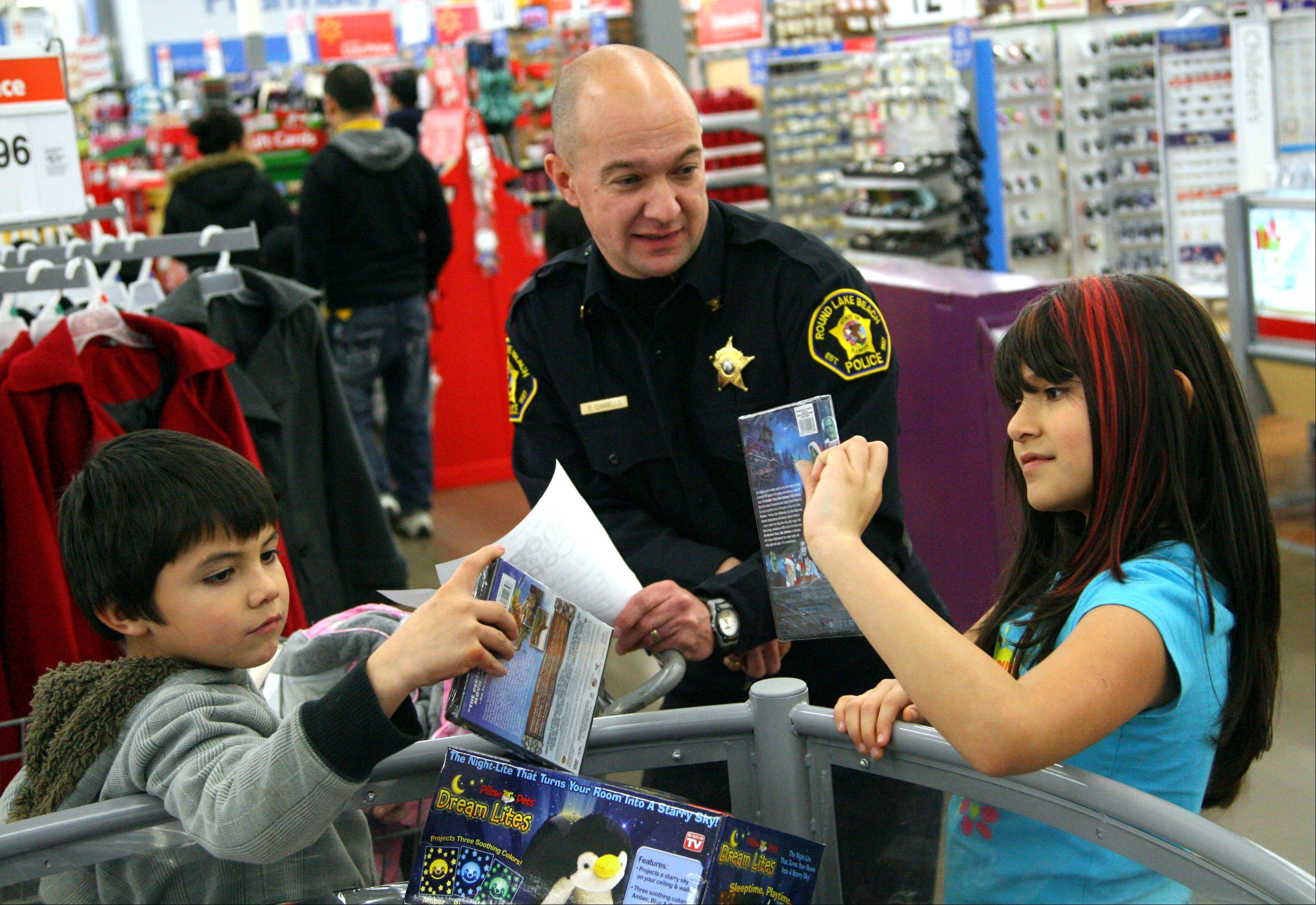 Round Lake Beach Deputy Police Chief Richard Chiarello helps 9-year-old Haley Falcon, right, and her brother Andrew, 8, select DVDs during the Shop with a Cop program. Round Lake Park police hosted the event for the 17th consecutive year.