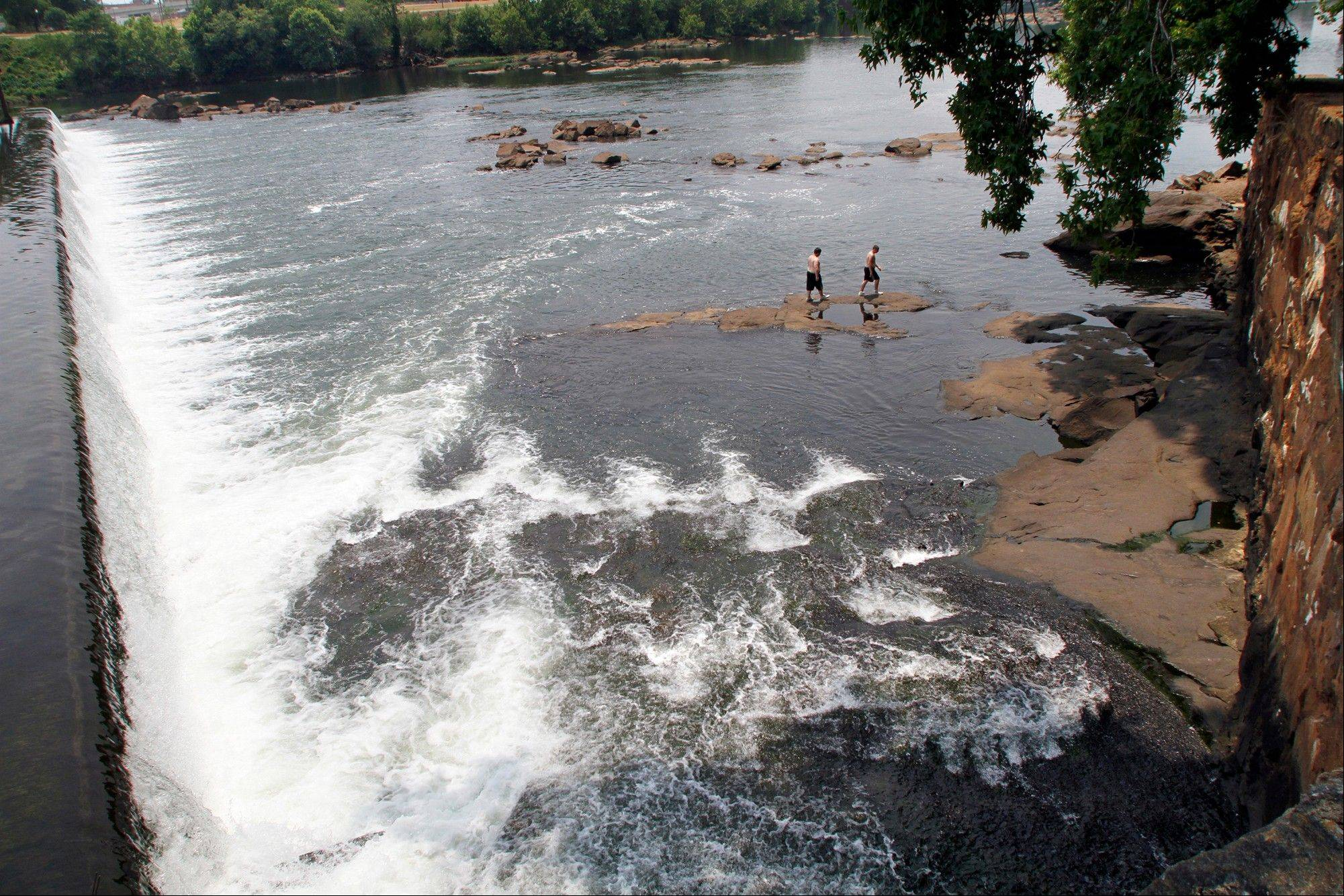 Men walk on the rocks in the Chattahoochee River below the City Mills dam near Columbus, Ga. Leaders of a national land trust say a river that runs through metro Atlanta holds the key to realizing a grand vision for outdoor enthusiasts.