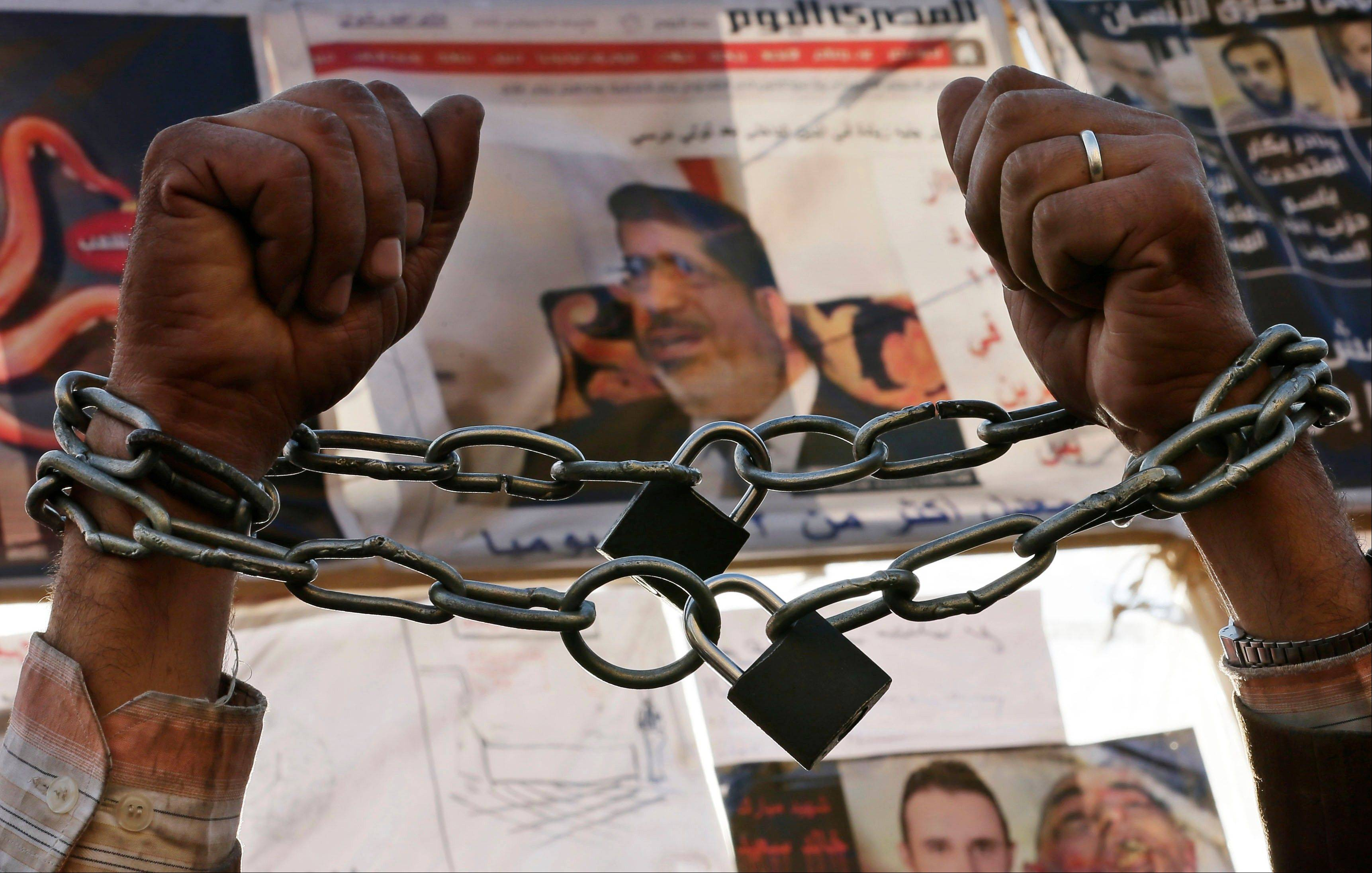 A protester chains his hands during a protest in Tahrir Square in Cairo, Egypt, Monday, Dec. 17, 2012. Egypt's political crisis shows no signs of abating as the opposition to the country's Islamist government levels new challenges against the legitimacy of a referendum on a draft constitution. Morsi also confronts criticism from the judiciary, as prosecutors hold a sit-in to demand removal of a new prosecutor general he appointed.