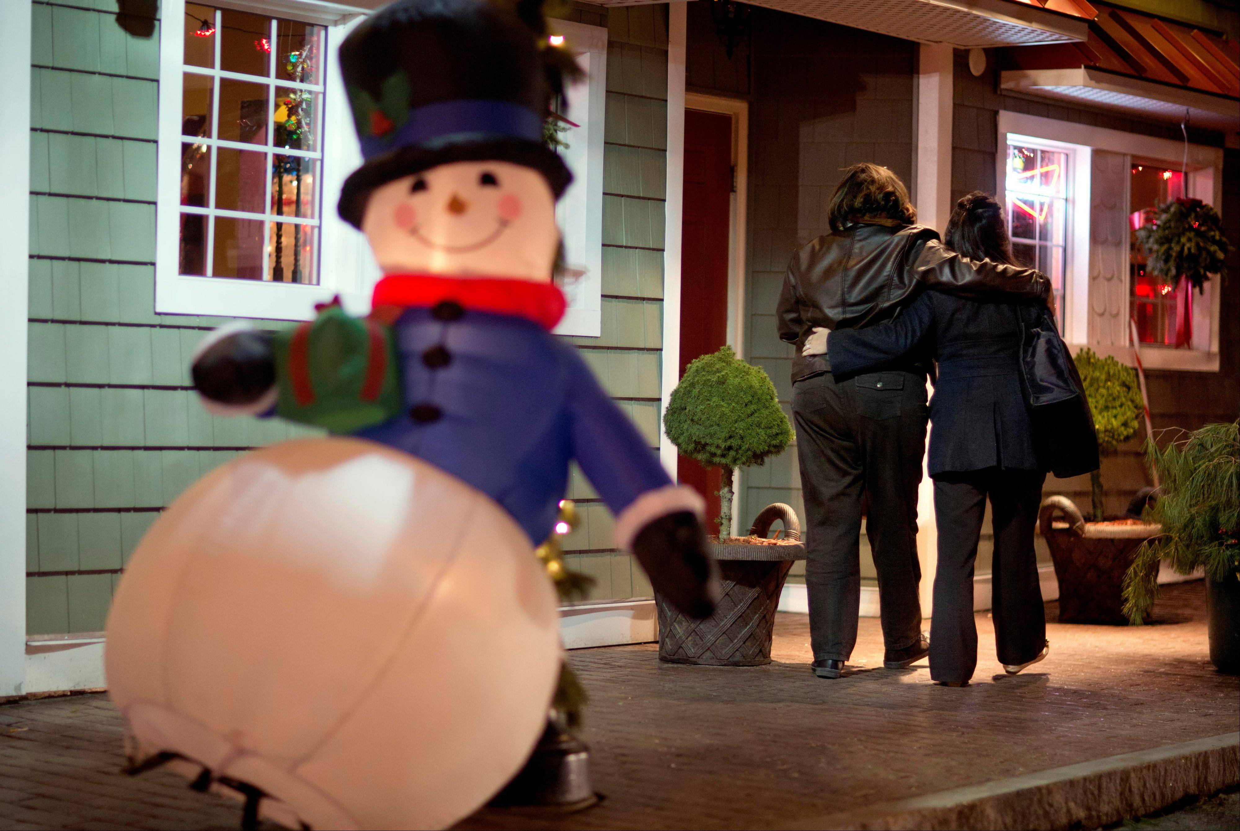In this Dec. 19, 2012 file photo, mourners walk past a Frosty the Snowman Christmas decoration after visiting a memorial for the Sandy Hook Elementary School shooting victims, in Newtown, Conn. In the wake of the shooting, the grieving town is trying to find meaning in Christmas. (AP Photo/David Goldman, File)