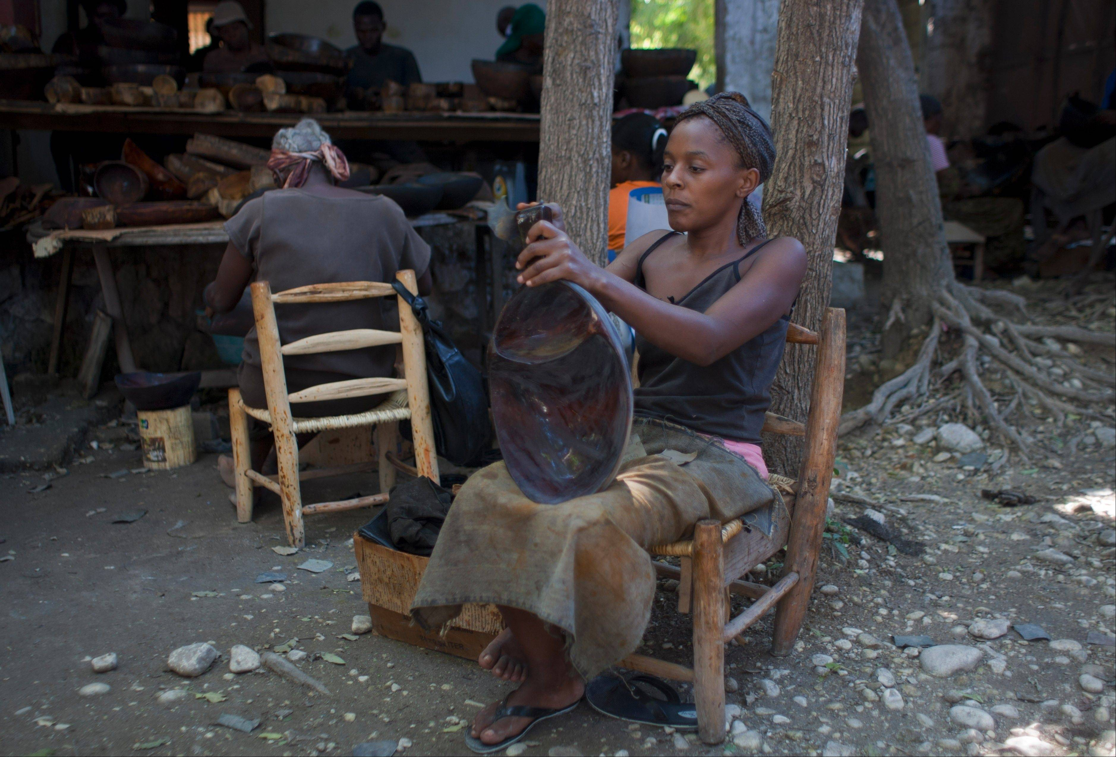Marleine Land, 24, creates a decorative wooden bowl at the Einstein wood shop in Carrefour, Haiti. At least three major U.S. retailers and three high-end designers are now working with at least five artisan groups to export Haitian arts and crafts.