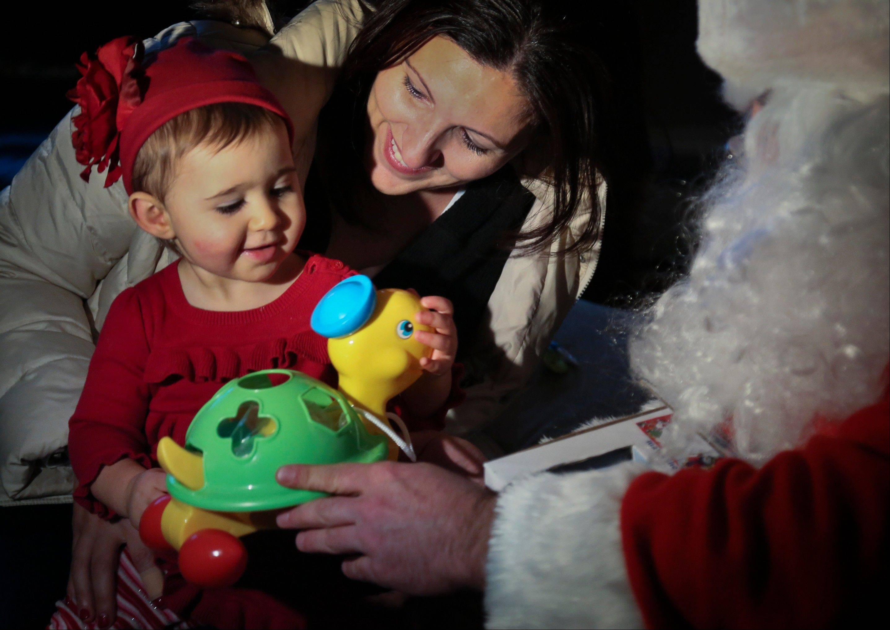 Elizabeth Sampol holds her daughter Ella, 14 months, who received a toy from Michael Sciaraffo, as Santa, in the Belle Harbor neighborhood of the Queens borough of New York. Using Facebook, Sciaraffo started a charitable enterprise to collect and personally deliver toys to children affected by Superstorm Sandy, dressed as Santa Claus.