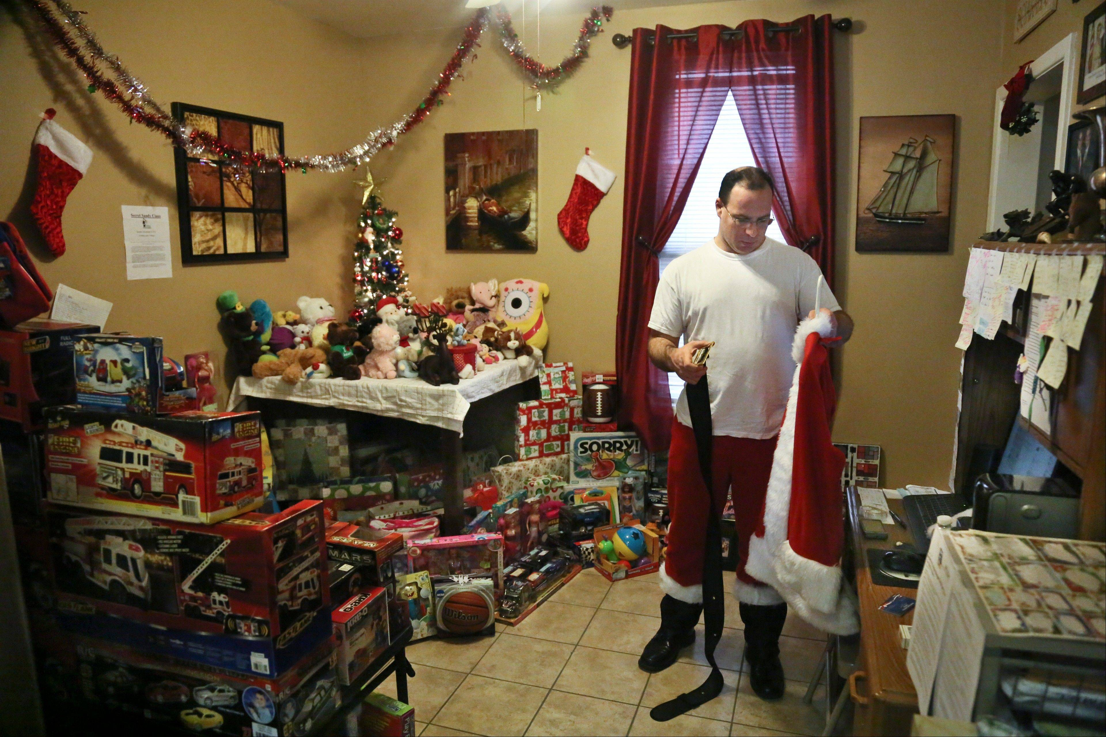 Michael Sciaraffo, a political consultant who has worked for Hillary Clinton and City Hall, is surrounded by donated toys as he prepares his Santa Claus costume, in the Brooklyn borough of New York. Using Facebook, Sciaraffo started a charitable enterprise to collect and personally deliver toys to children affected by Superstorm Sandy victims dressed as Santa Claus.