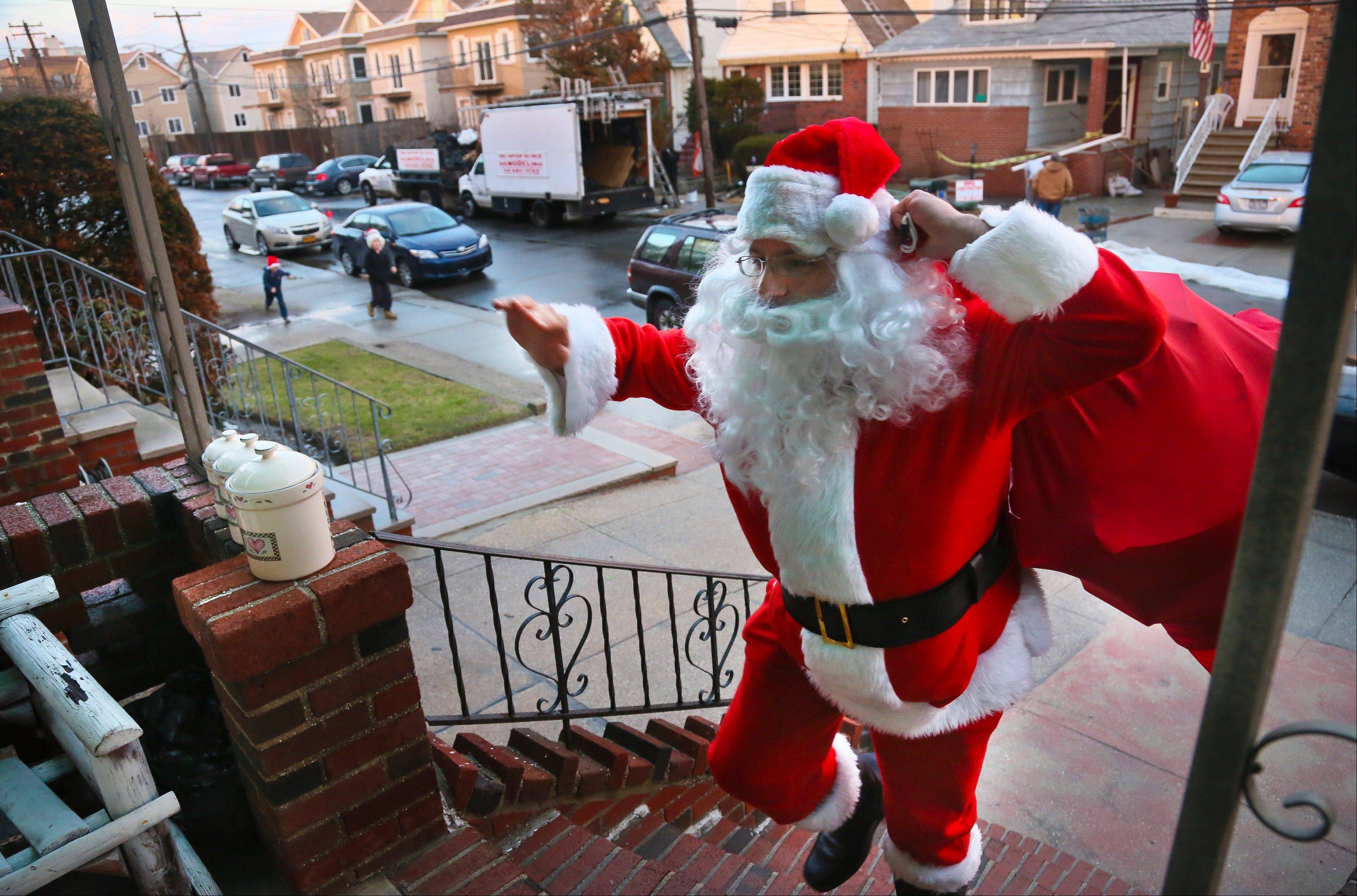 Michael Sciaraffo, as Santa Claus, arrives at the home of the Creamer family to deliver toys in the Belle Harbor neighborhood of the Queens borough of New York. Using Facebook, Sciaraffo started a charitable enterprise to collect and personally deliver toys to children affected by superstorm Sandy, dressed as Santa Claus.