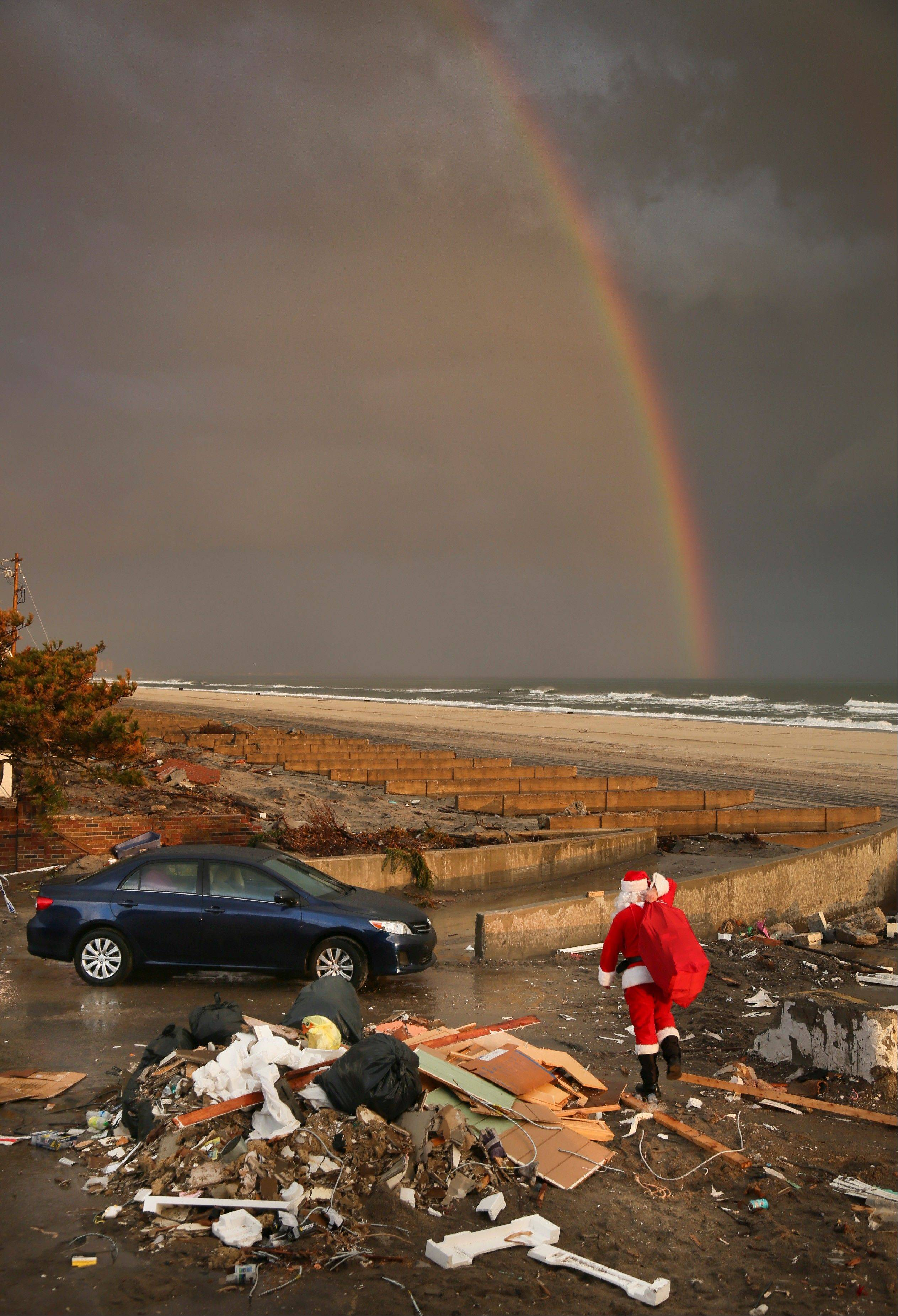 A rainbow appears as a Santa-dressed Michael Sciaraffo leaves the home of Ella Sampol, 14 months, after bringing her a toy in the Belle Harbor neighborhood of the Queens borough of New York. Using Facebook, Sciaraffo started a charitable enterprise to collect and personally deliver toys to children affected by Superstorm Sandy, dressed as Santa Claus.