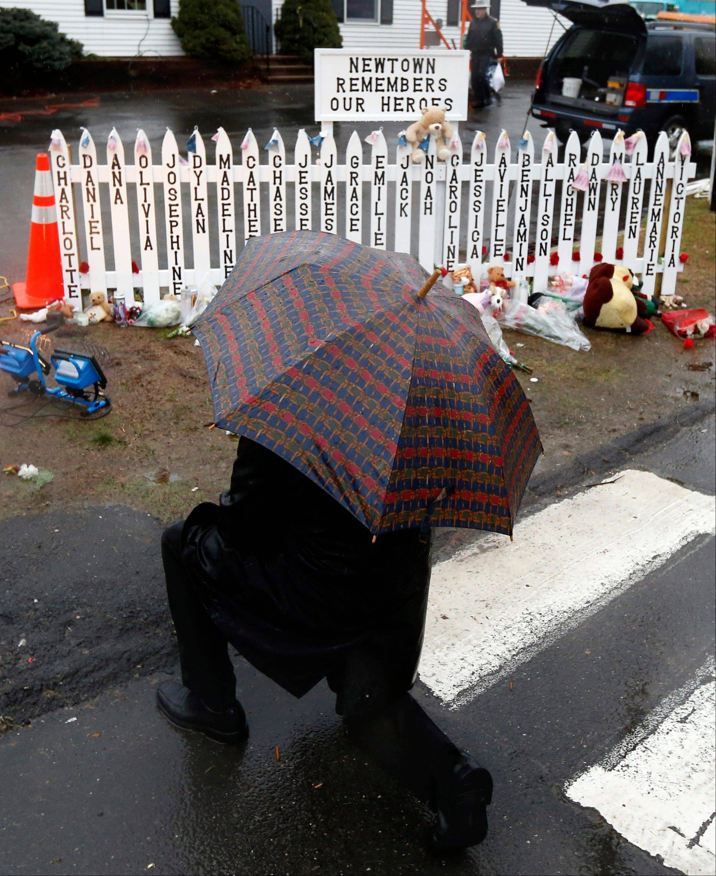 A man kneels in front of a makeshift memorial Friday during a moment of silence at 9:30 a.m. in Newtown, Conn. The chiming of bells reverberated throughout Newtown, commemorating one week since the crackle of gunfire in a schoolhouse killed 20 children and six adults in a massacre that has shaken the community and the nation.
