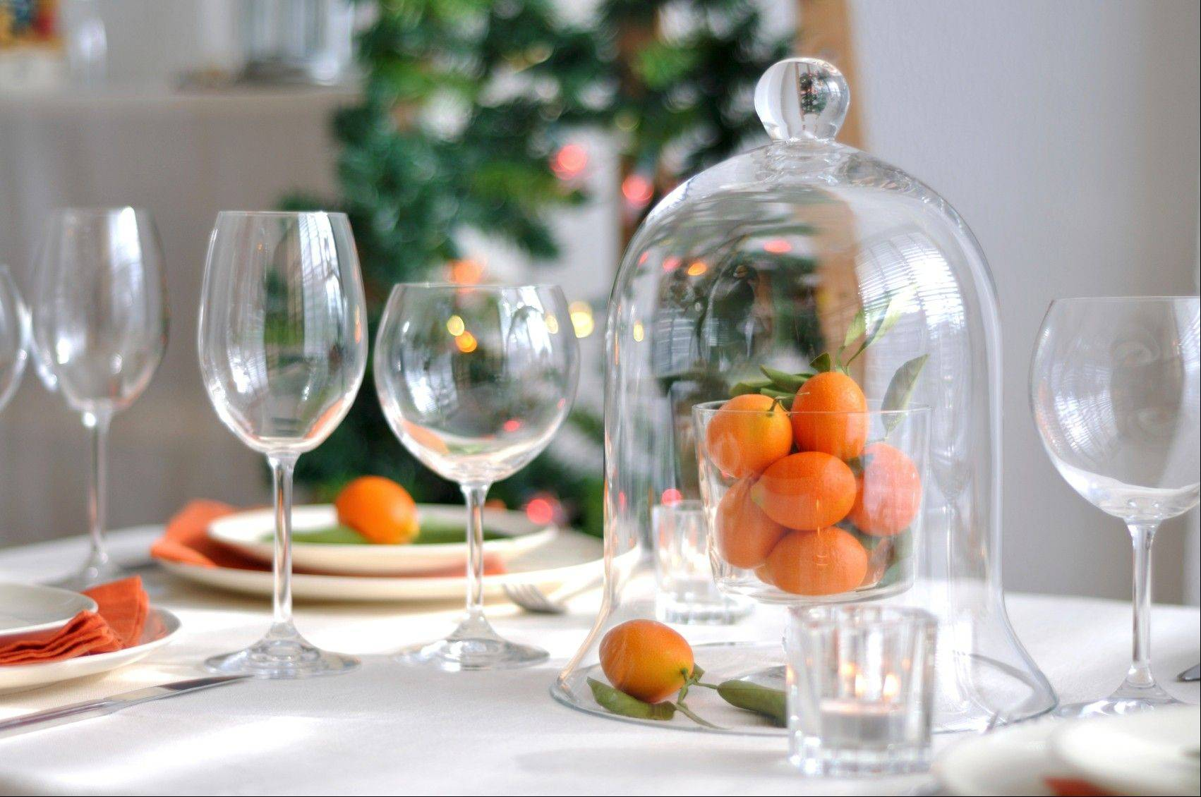 Bright orange napkins and natural decor like oranges and kumquats add a punch of color to the tabletop.
