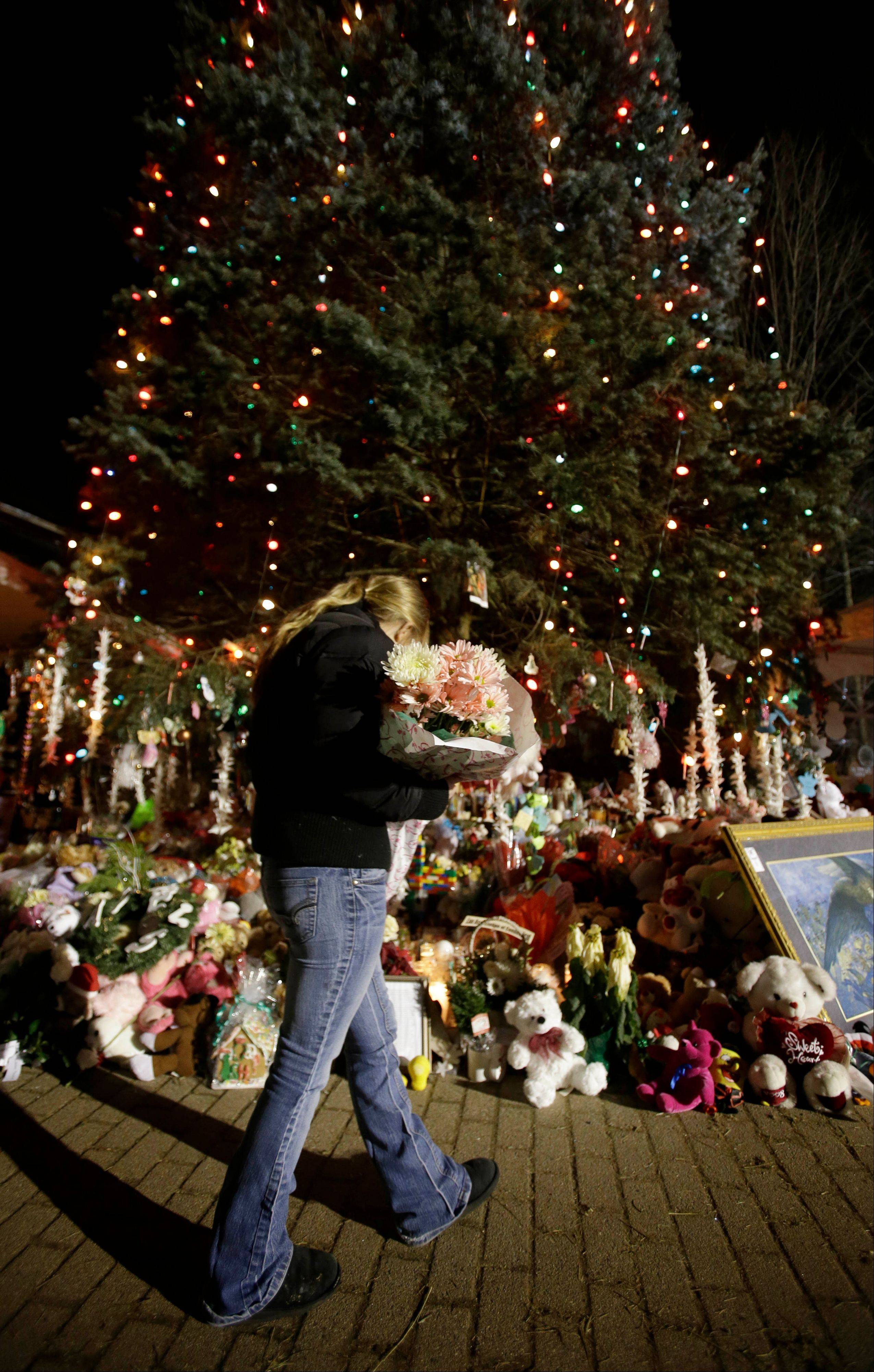 In this Thursday, Dec. 20, 2012 file photo, a woman with flowers walks past a Christmas tree which has become a memorial to the Newtown shooting victims in Newtown, Conn. In the wake of the shooting, the grieving town is trying to find meaning in Christmas.