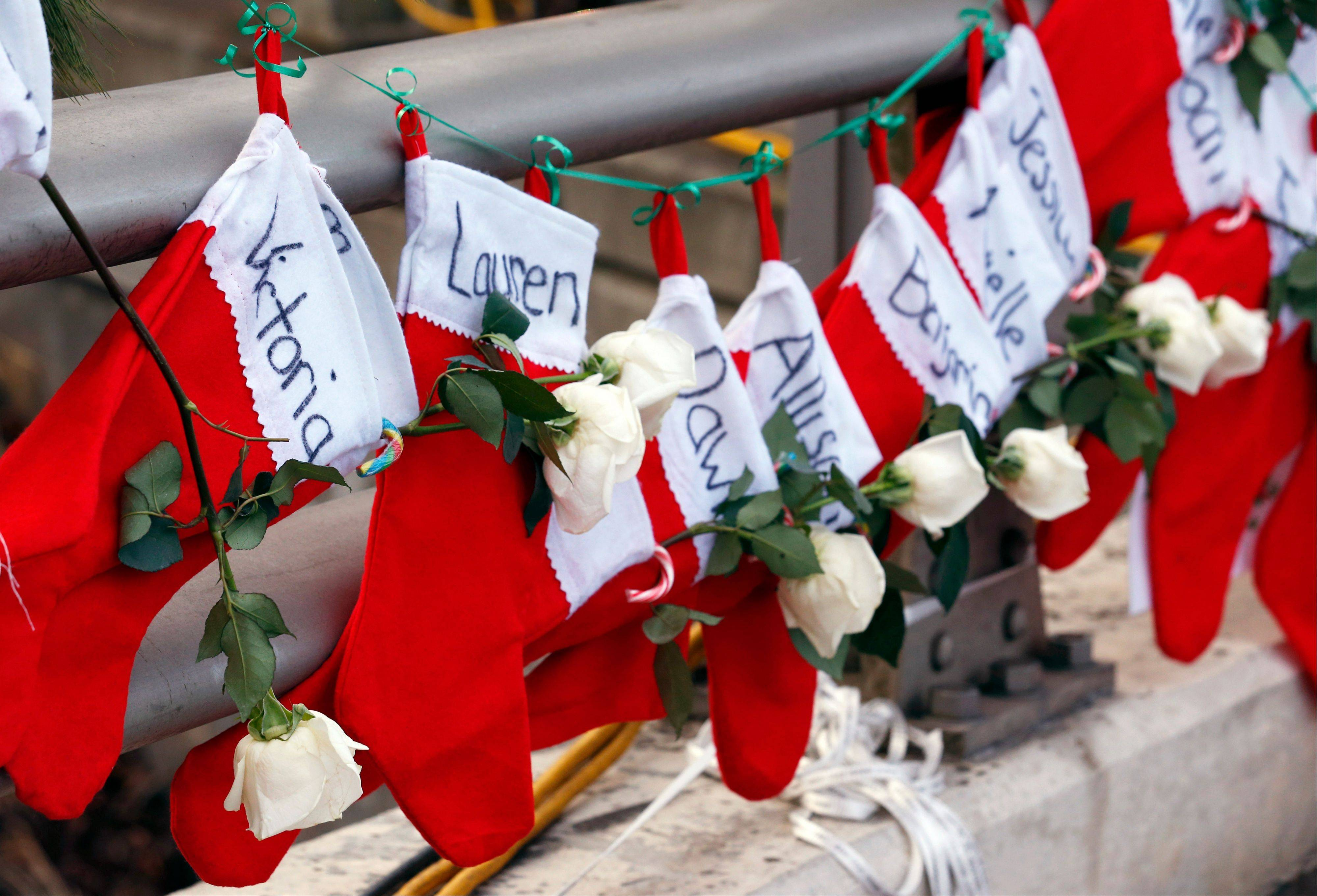In this Wednesday, Dec. 19, 2012 file photo, Christmas stockings with the names of shooting victims hang from railing near a makeshift memorial near the town Christmas tree in the Sandy Hook village of Newtown, Conn. In the wake of the shooting, the grieving town is trying to find meaning in Christmas.
