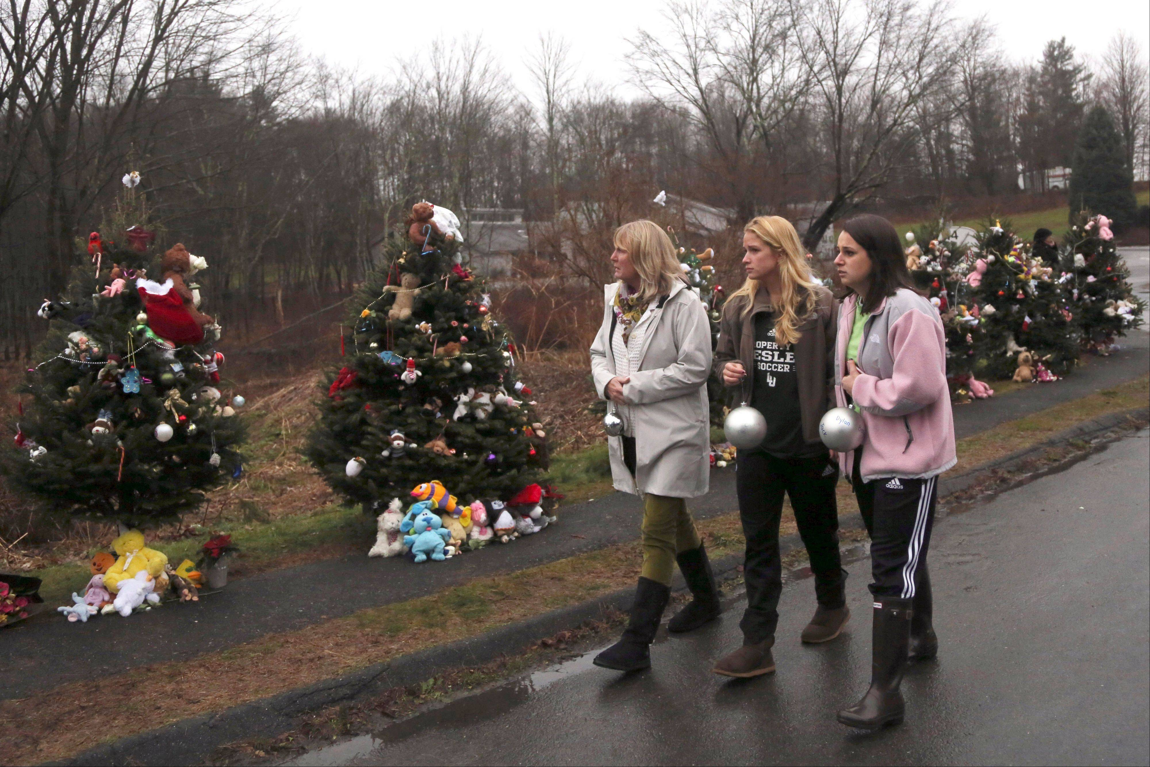 In this Monday, Dec. 17, 2012 file photo, mourners carry ornaments to decorate the Christmas trees at one of the makeshift memorials for the Sandy Hook Elementary School shooting victims, in Newtown, Conn. In the wake of the shooting, the grieving town is trying to find meaning in Christmas.
