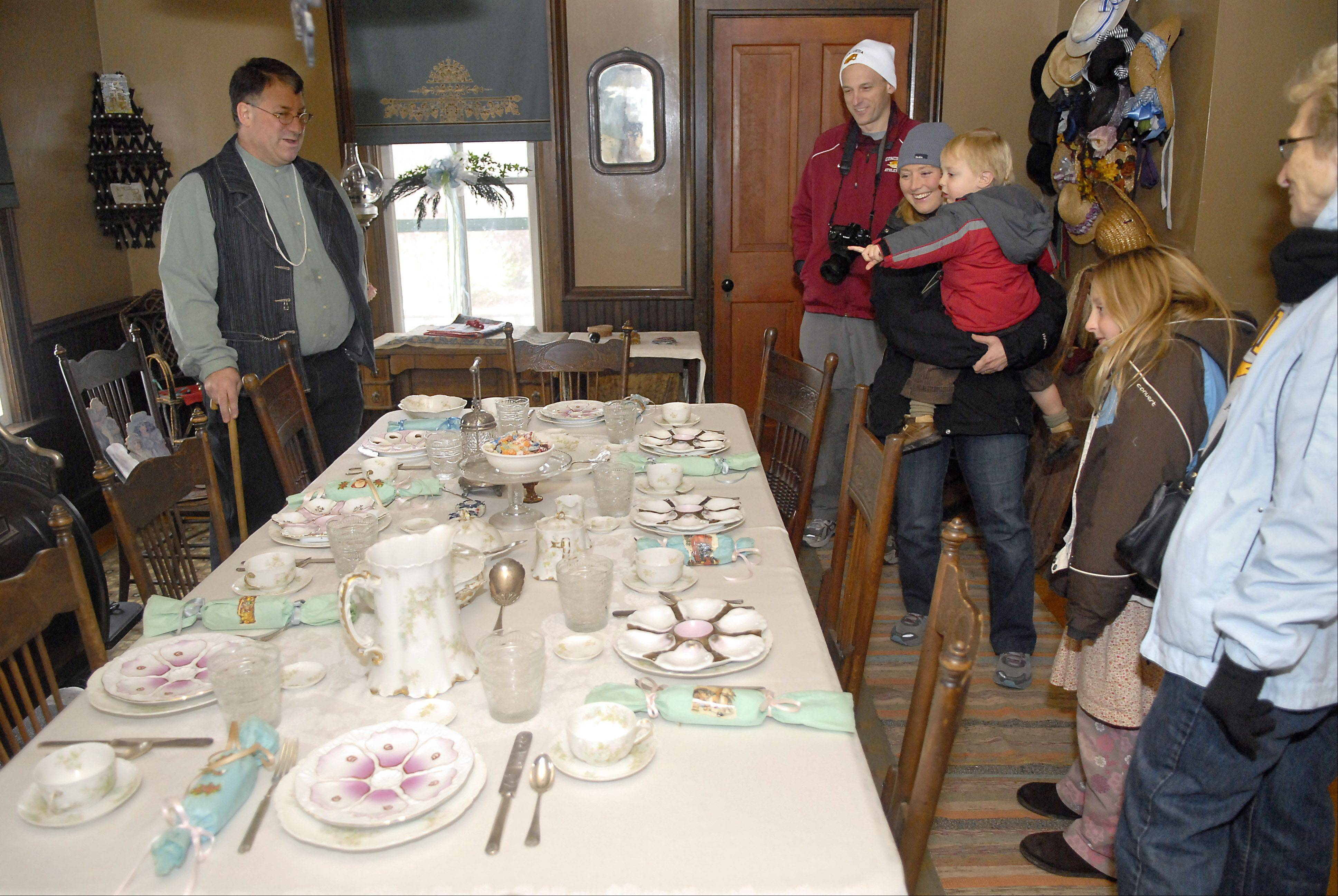 Heritage Interpreter Wayne Hill talks to the Beisel family of Elmhurst on Sunday about how tables were set for Christmas during the 1890s. The Beisels were visiting Kline Creek Farm in West Chicago, which is offering tours of its farmhouse to give visitors a sense of how the holidays were celebrated in the late 19th century. Matt and Jill Beisel, holding Jonah, 2, bring their family to the farm four or five times a year. Keegan, 8, and her grandmother, Floris Beisel, are on the right.