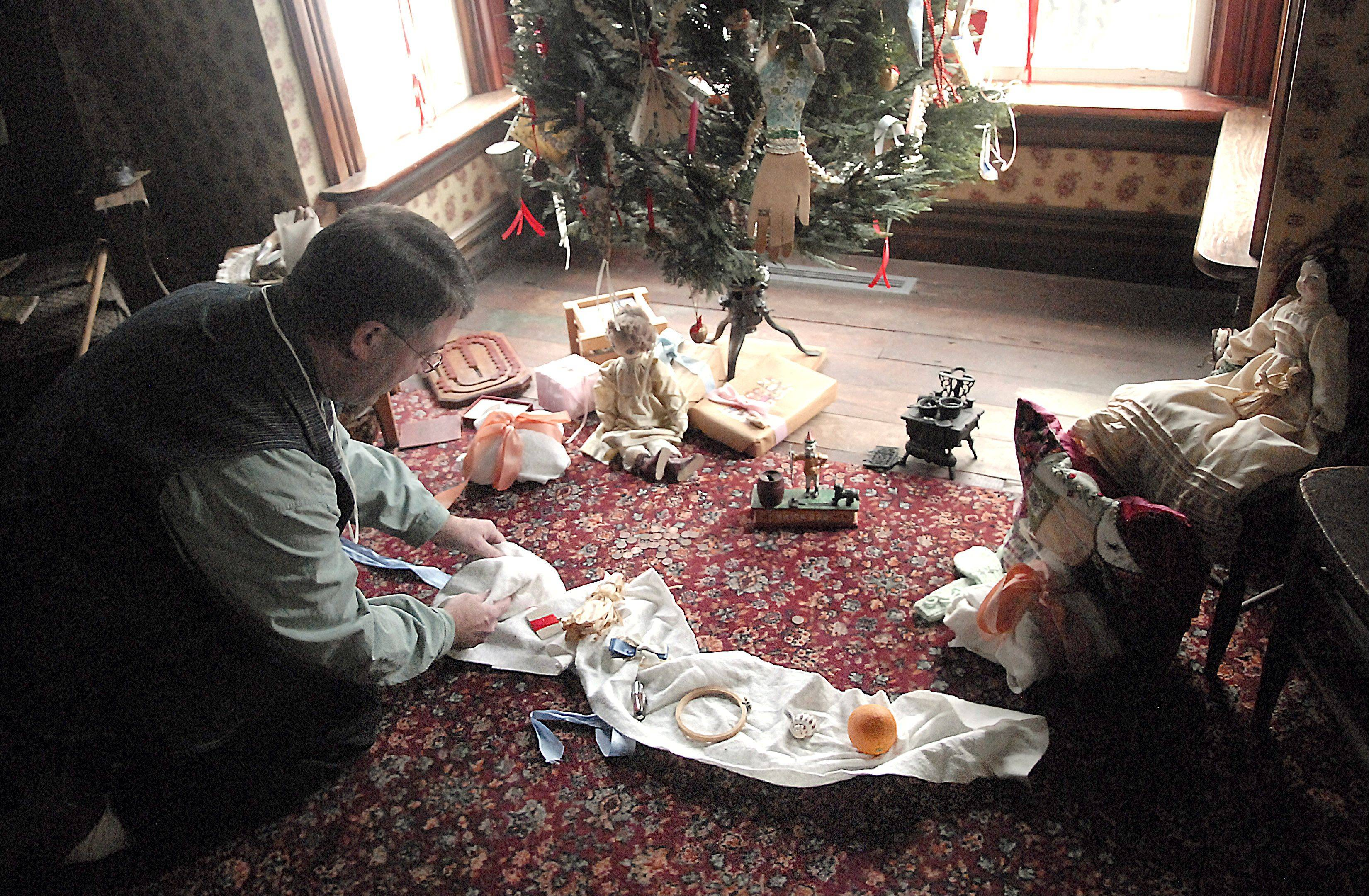 Wayne Hill, Heritage Interpreter at Kline Creek Farm, shows how presents were wrapped in one long sheet of material. Children would take turns unrolling the wrapped package, and whatever they unveiled was their gift.