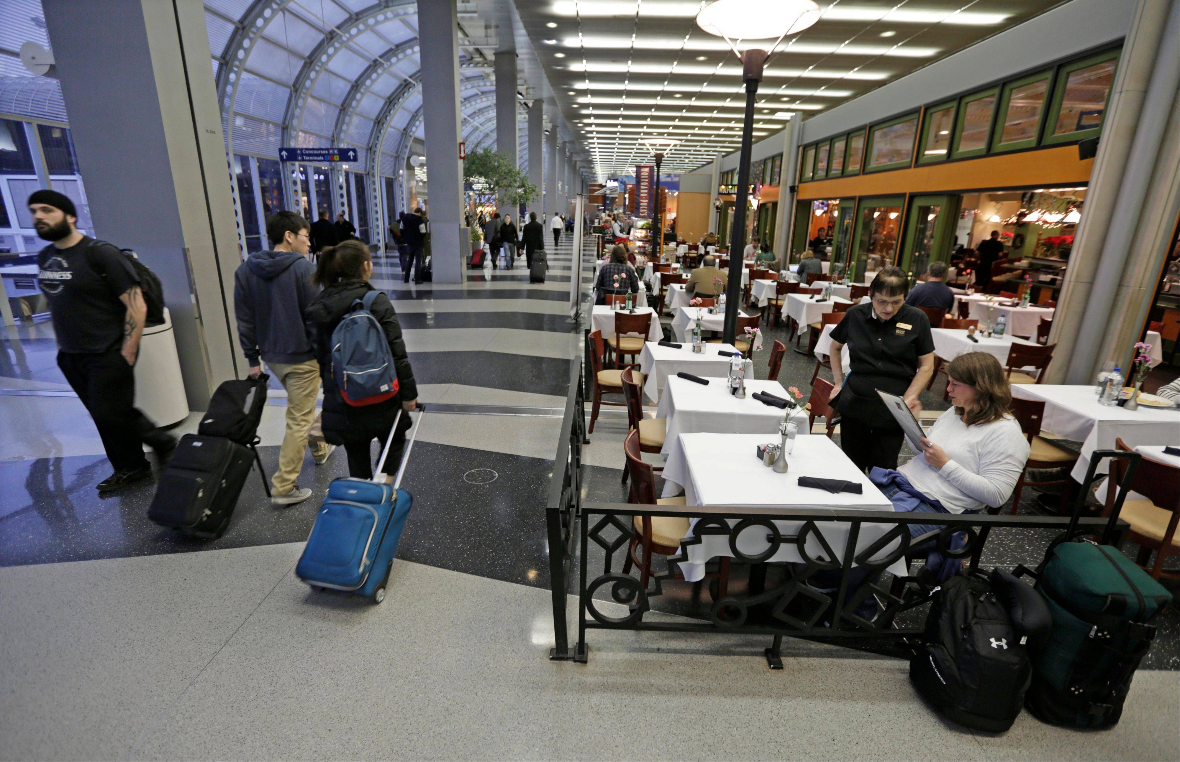 In this photo taken Tuesday, Dec. 18, 2012, at O'Hare International Airport in Chicago, a diner at Wolfgang Puck Cafe sits in a sidewalk cafe setting in Terminal 3.