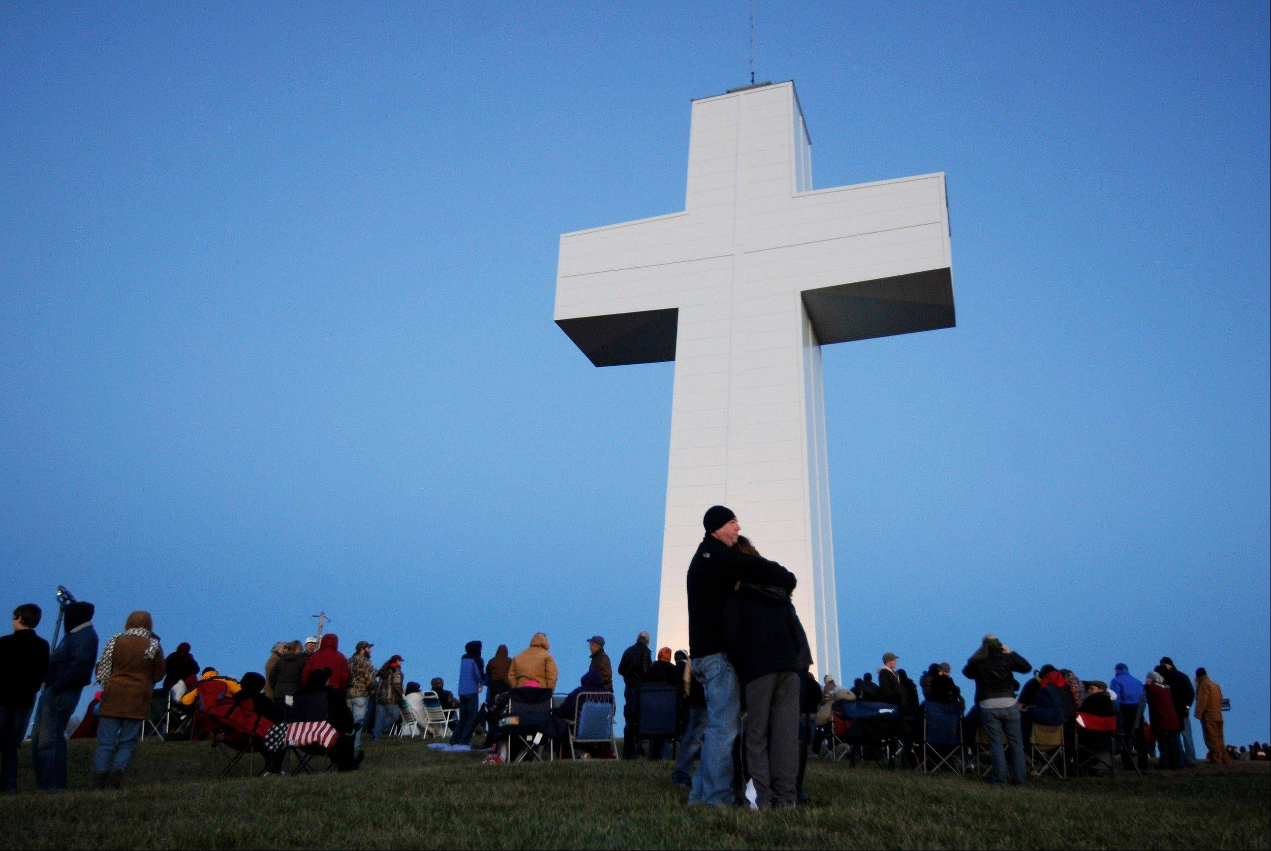 Spectators huddle together for warmth before the lighting of the Bald Knob Cross of Peace Saturday in downstate Alto Pass. The lighting ceremony marked the completion of a renovation project that began in 2009.