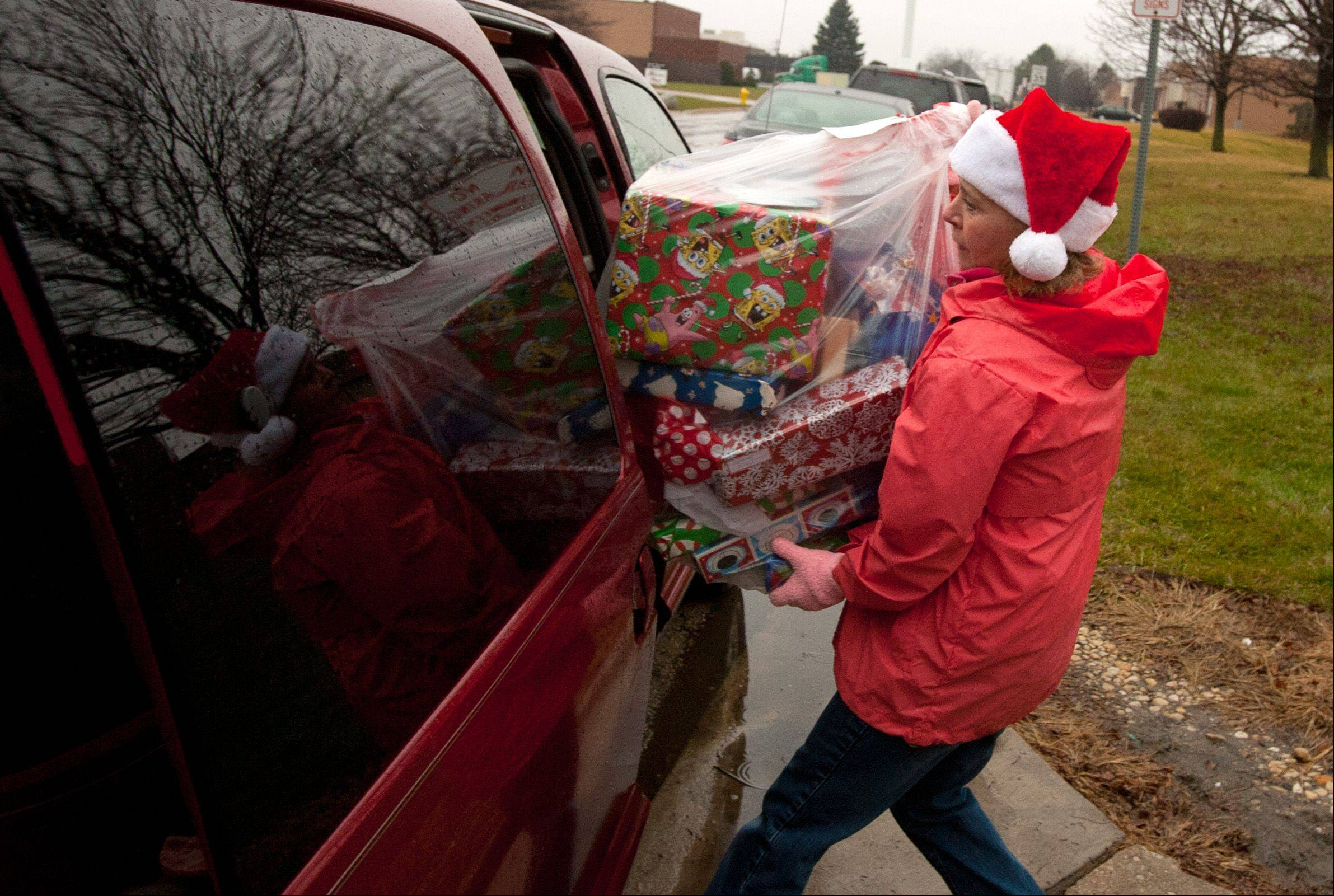 Jan Bolsoni of Glen Ellyn, a member of Peace Lutheran Church in Lombard, loads presents as the Humanitarian Service Project distributes holiday packages to area families in need.