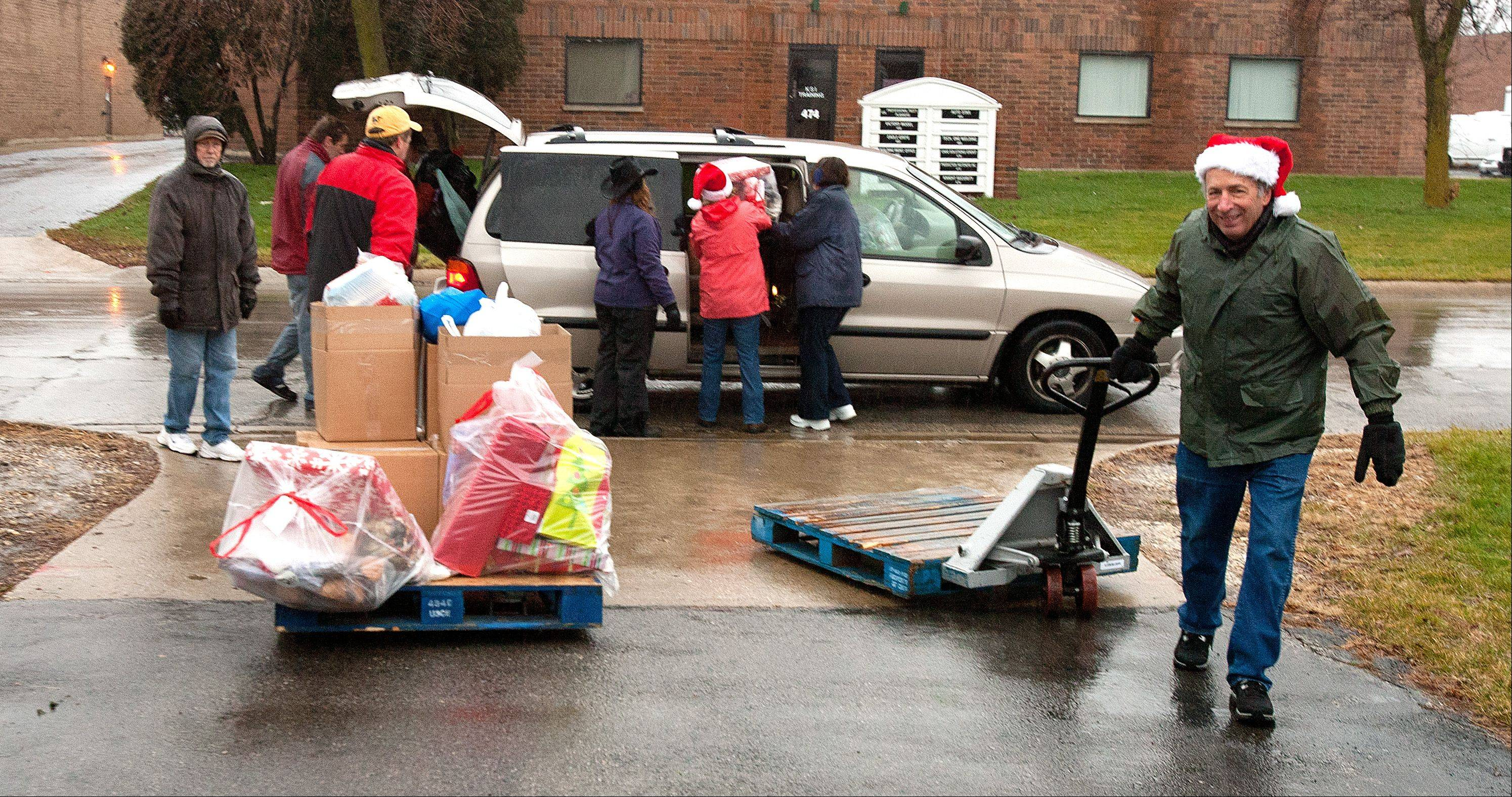 Mike Bolsoni, right, of Glen Ellyn, a member of Peace Lutheran Church in Lombard, loads presents as part of a Humanitarian Service Project.