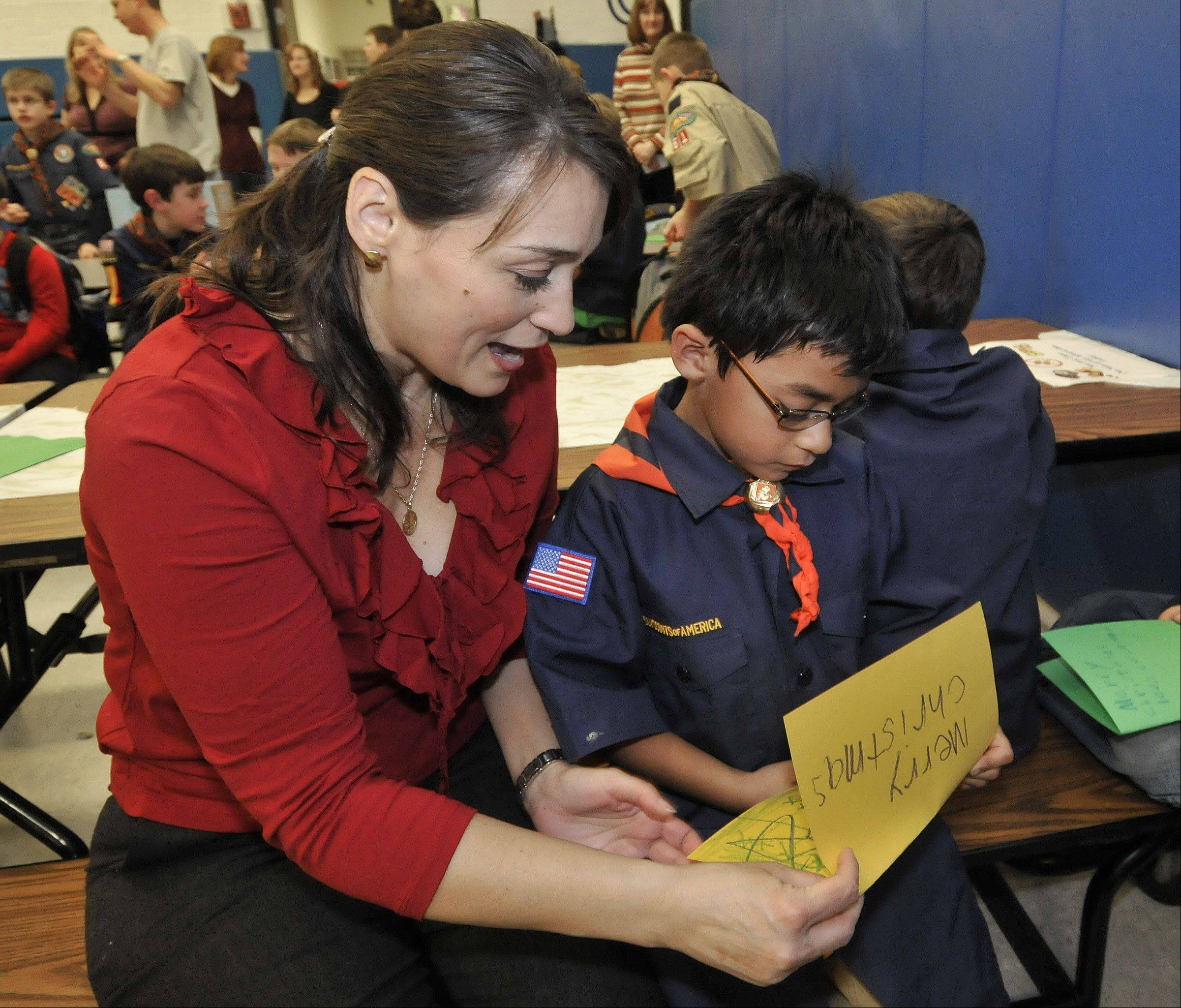 Esteban Hernandez shows his Christmas card to his mother, Belinda Hernandez. Cub Scouts from Whittier School in Wheaton wrote cards and packed gifts that were distributed Saturday to veterans in the Midwest Shelter for Homeless Veterans in Wheaton.