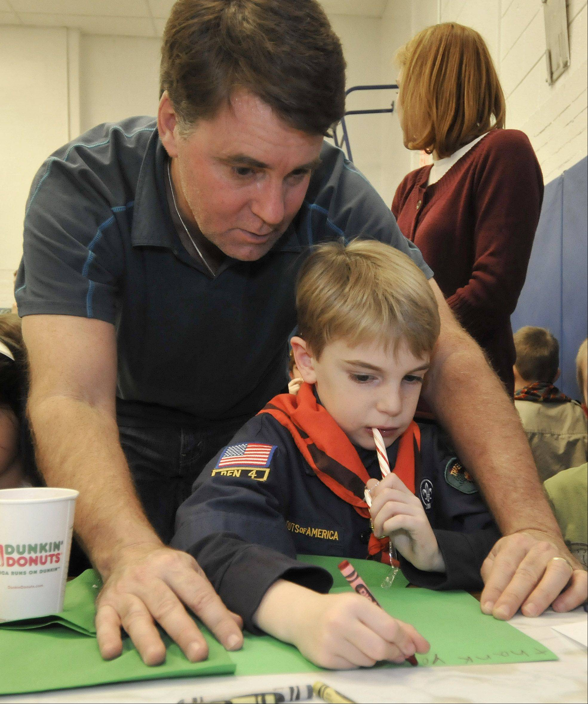 Matt Ellison helps his son, Addison, as he combines his snack with creating his Christmas card. Members of Cub Scout Pack 61 helped raise money to purchase holiday gifts for five vets at the Midwest Shelter for Homeless Veterans in Wheaton.