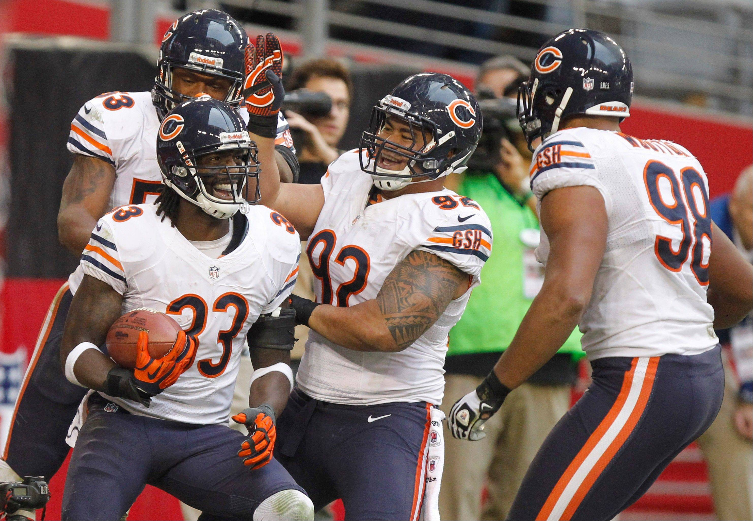 Chicago Bears cornerback Charles Tillman (33) celebrates his touchdown with teammates Stephen Paea (92), Nick Roach (53) and Corey Wootton (98) during the second half.