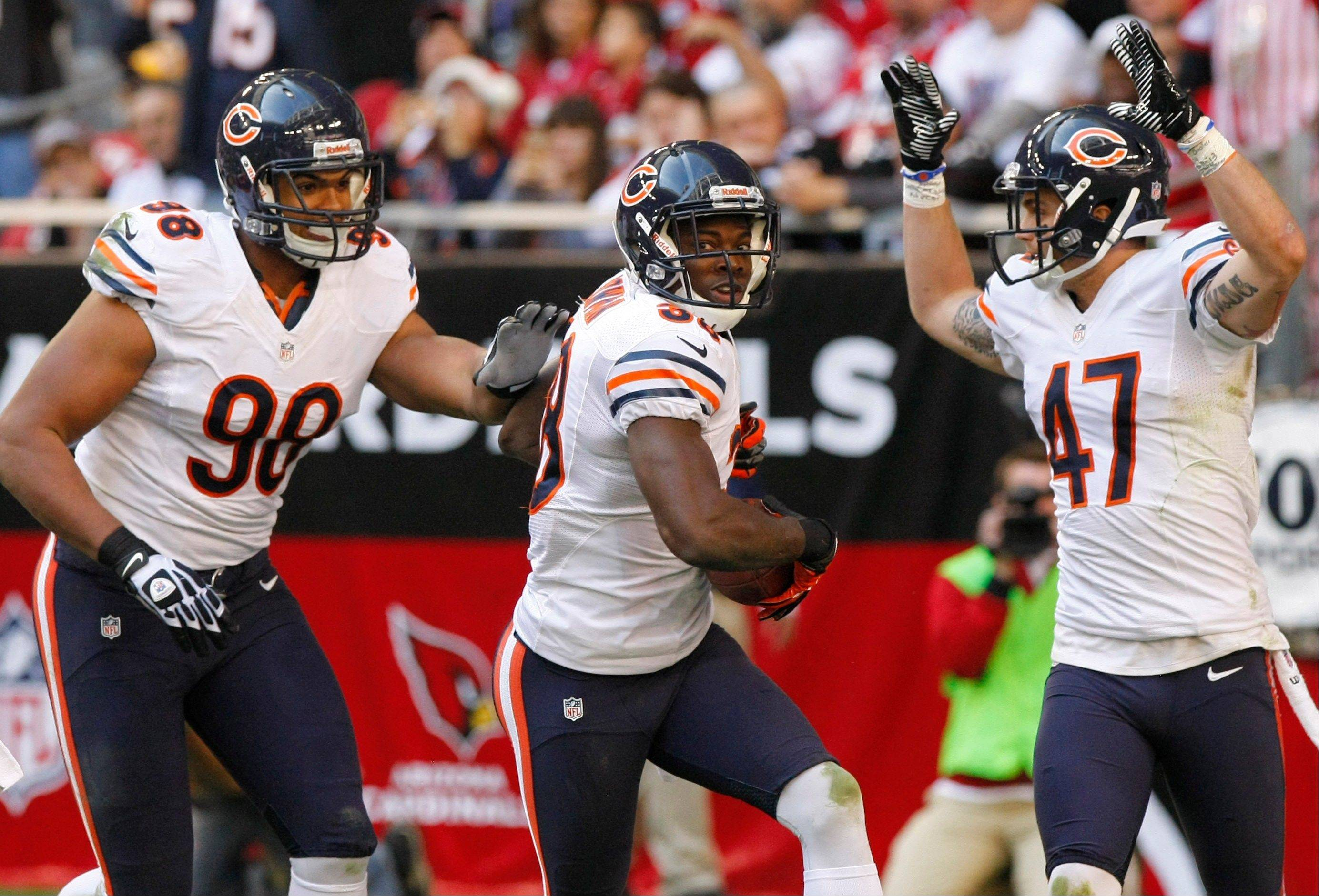 Chicago Bears defensive back Zack Bowman celebrates his touchdown with teammates Corey Wootton (98) and Chris Conte (47) during the first half.