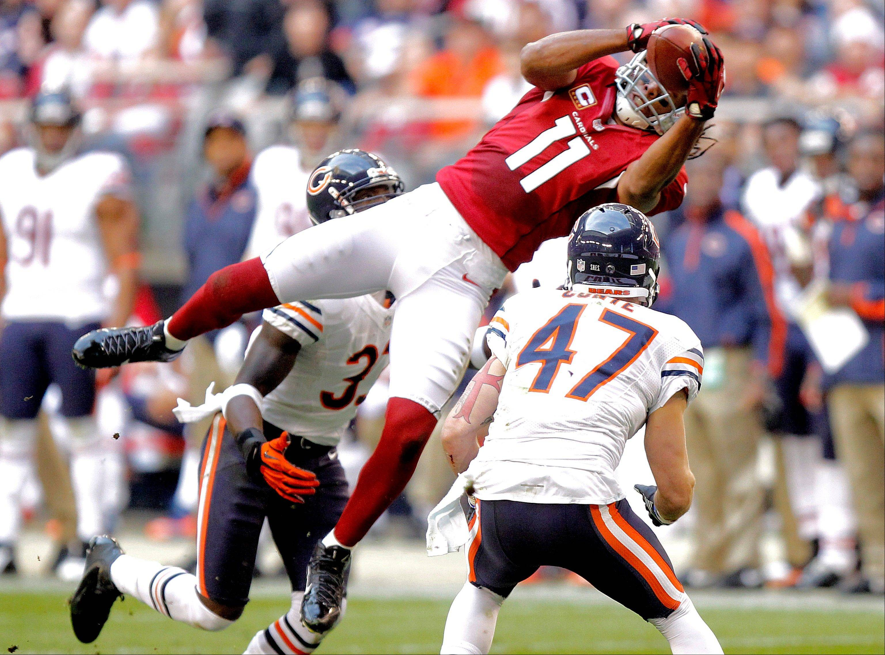 Arizona Cardinals wide receiver Larry Fitzgerald leaps for a pass as Chicago Bears free safety Chris Conte defends during the first half.