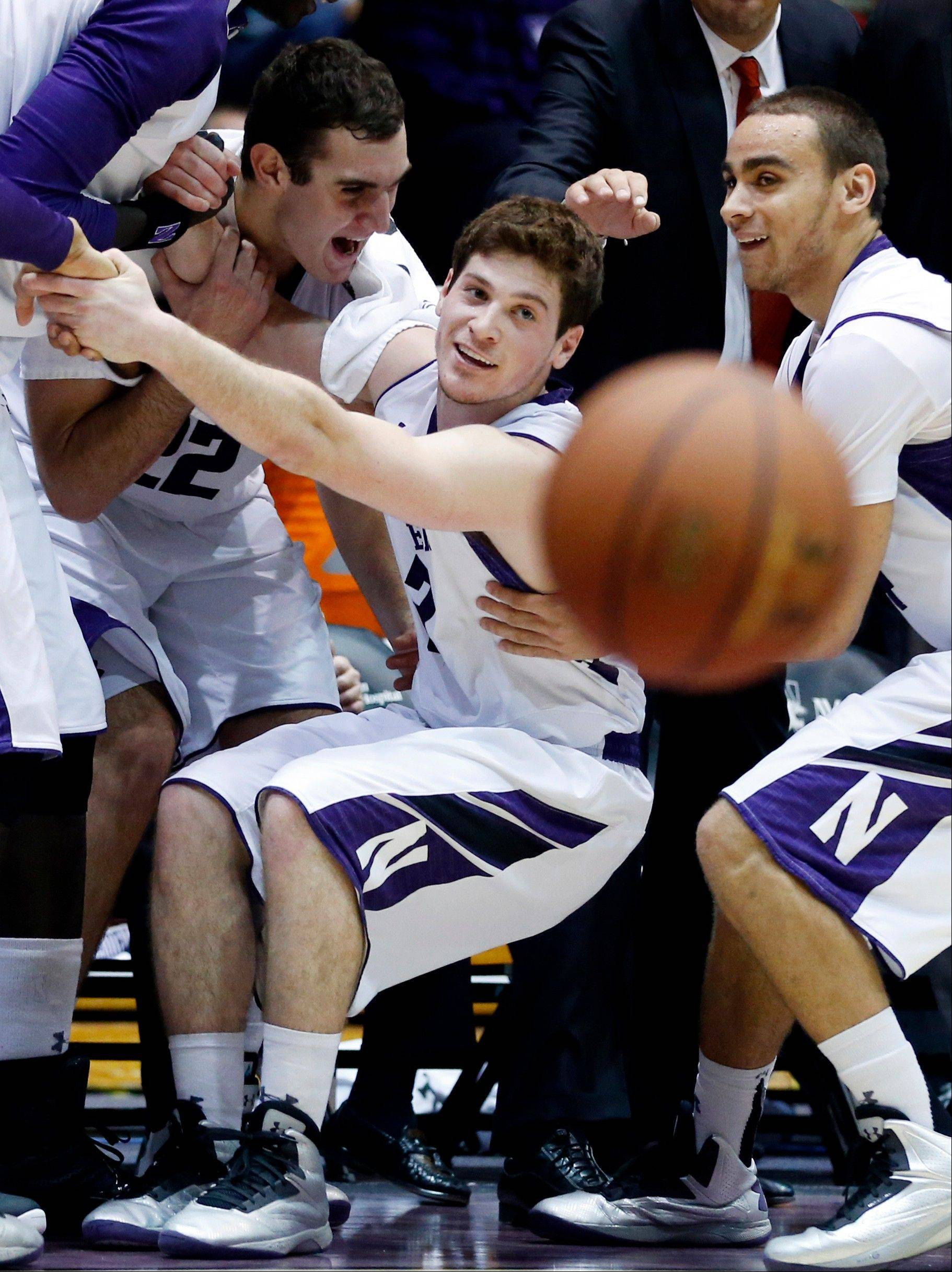 Northwestern guard Dave Sobolewski, center, celebrates with center Alex Plah, left, and guard Tre Demps after scoring a three-point basket during the second half of an NCAA college basketball game against Brown in Evanston, Ill., Sunday, Dec. 23, 2012. Northwestern won 63-42.