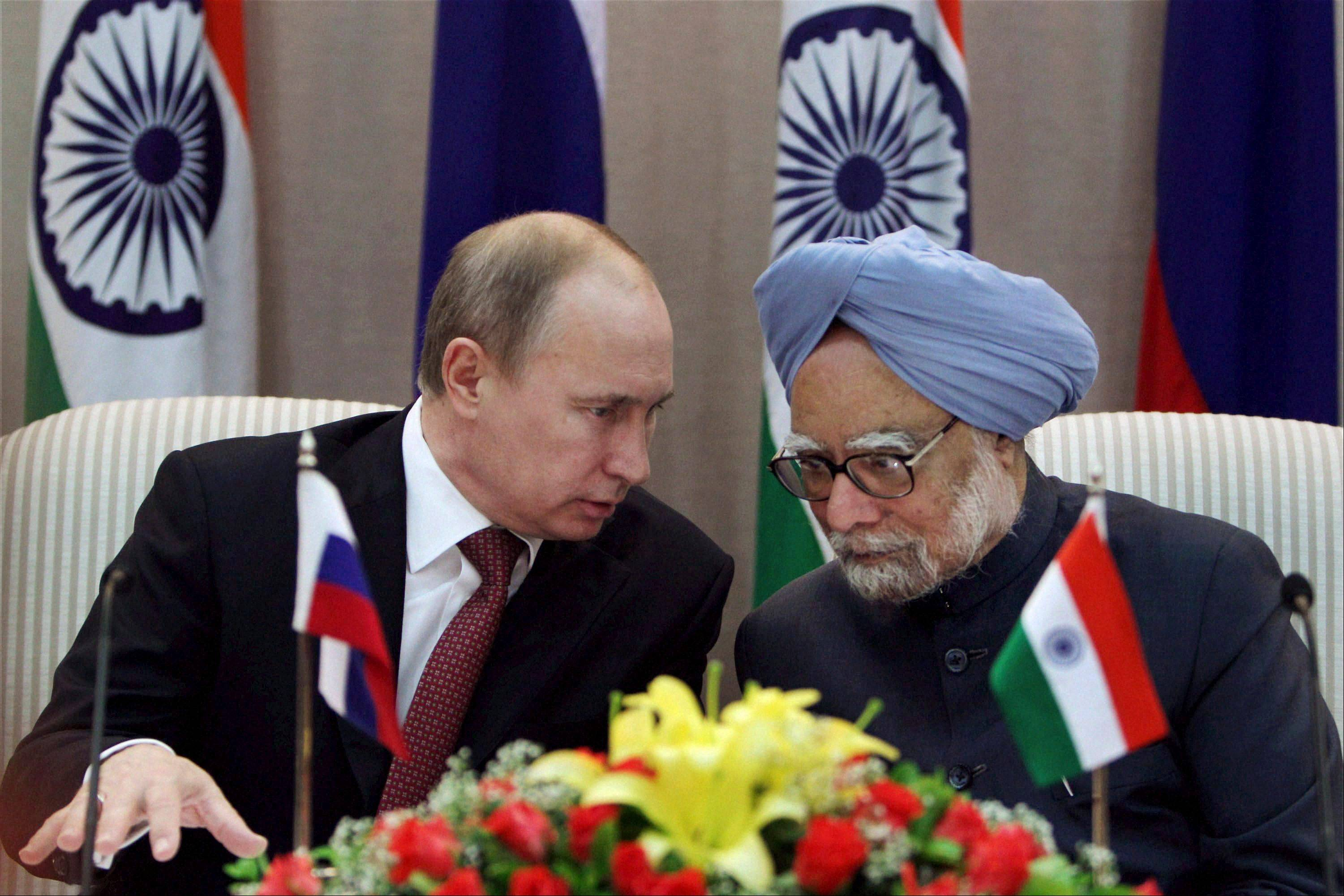 Russian President Vladimir Putin, left, talks to Indian Prime Minister Manmohan Singh at a joint press conference following their meeting in New Delhi, India, Monday, Dec. 24, 2012. Russia and India signed weapons deals worth billions of dollars Monday as President Vladimir Putin sought to further boost ties with an old ally.