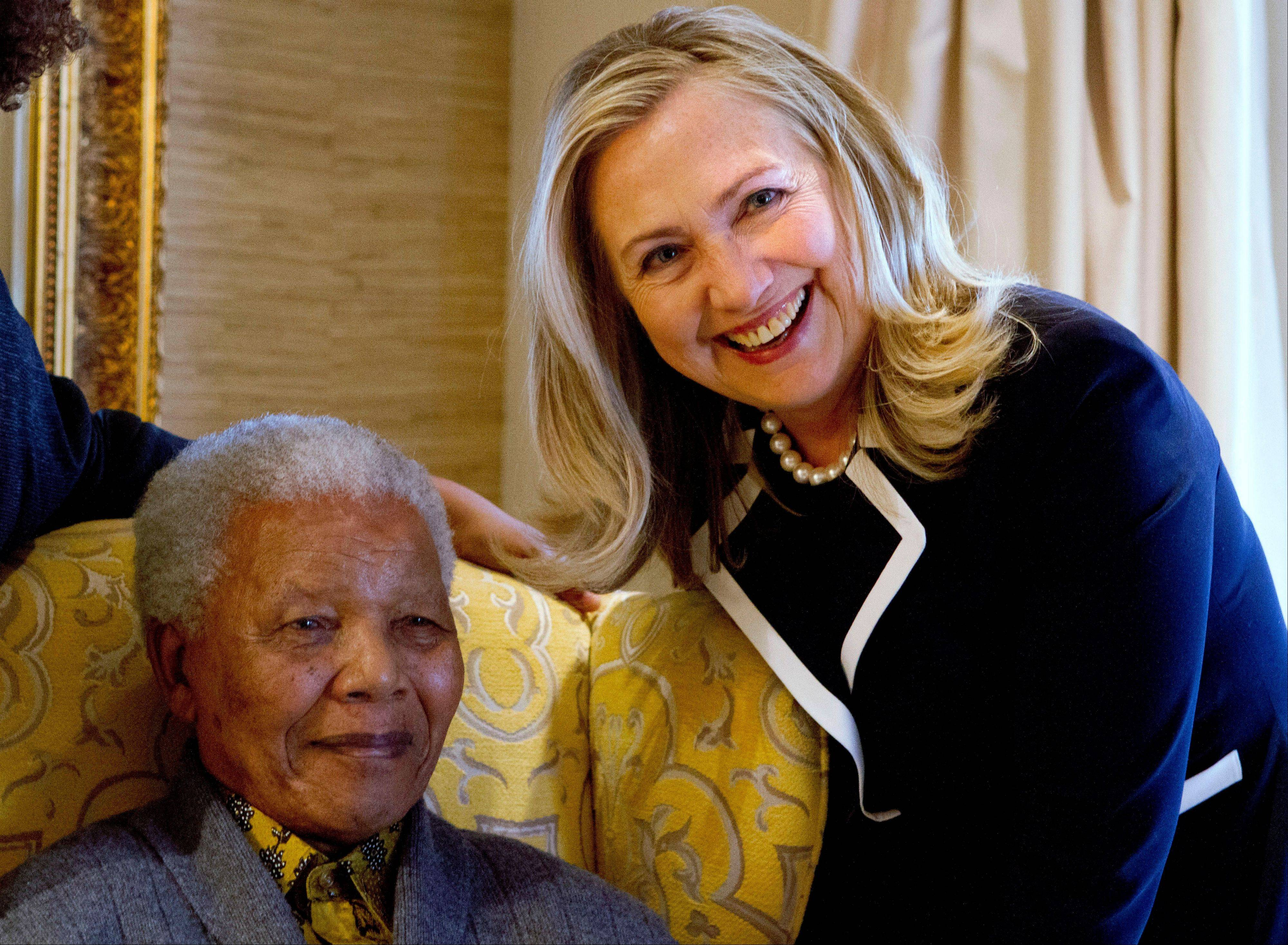 In this Aug. 6, 2012 file photo, U.S. Secretary of State Hillary Rodham Clinton, right, meets with former South Africa President Nelson Mandela, 94, at his home in Qunu, South Africa. There may be no living figure so revered as Mandela around the world as a symbol of sacrifice and reconciliation, his legacy forged in the fight against apartheid, the system of white minority rule that imprisoned him for 27 years.