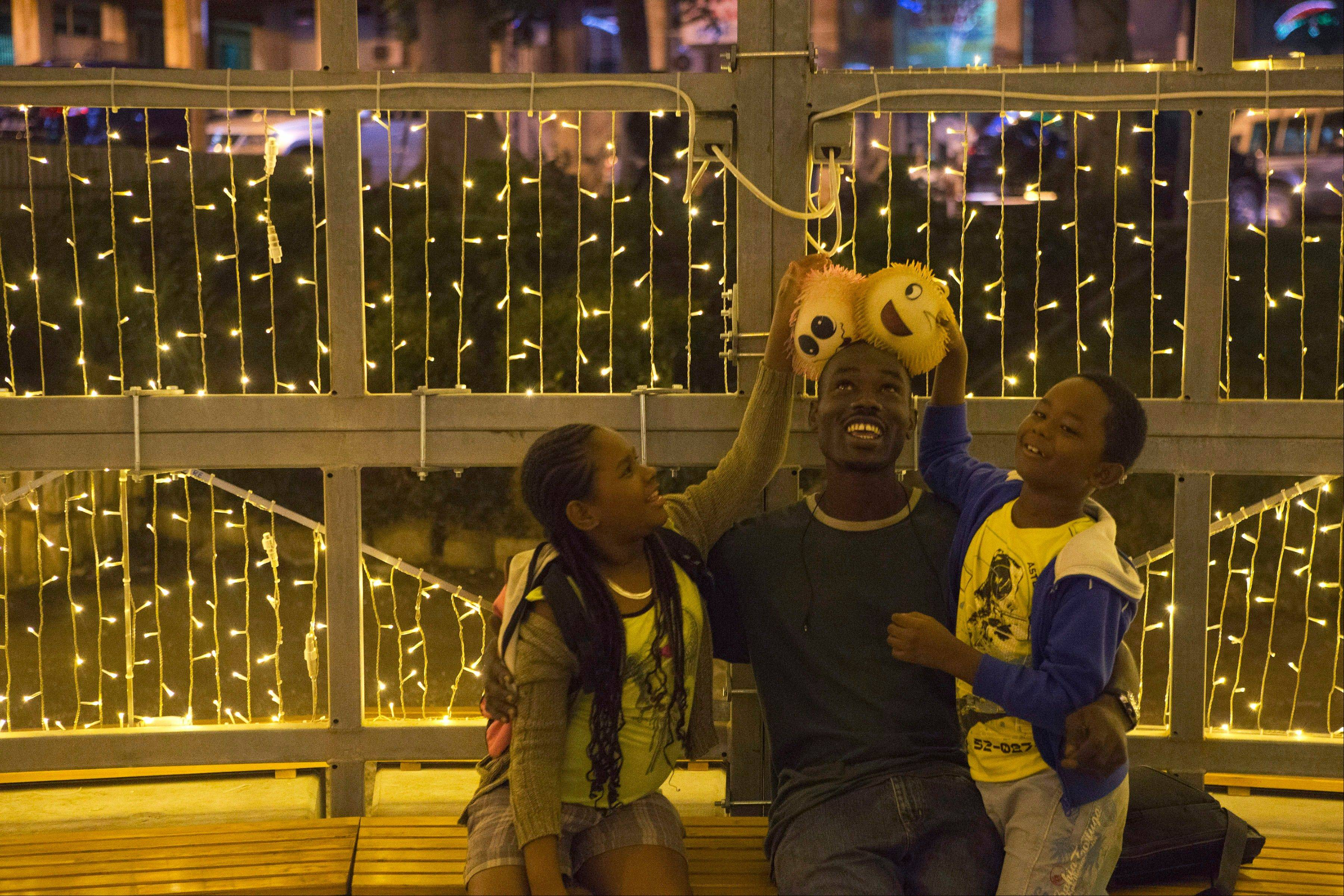 Kids play with their uncle with newly bought Christmas toys, as they visit a display of lights in central Dakar, Senegal. As Christmas approaches in mostly Muslim Senegal, vendors ply the streets selling tinsel, artificial trees, and inflatable Santas, and the main boulevards are all aglow in holiday lights. Senegal, a moderate country along Africa�s western coast, has long been a place where Christians and Muslims coexist peacefully and share in each other�s holidays.