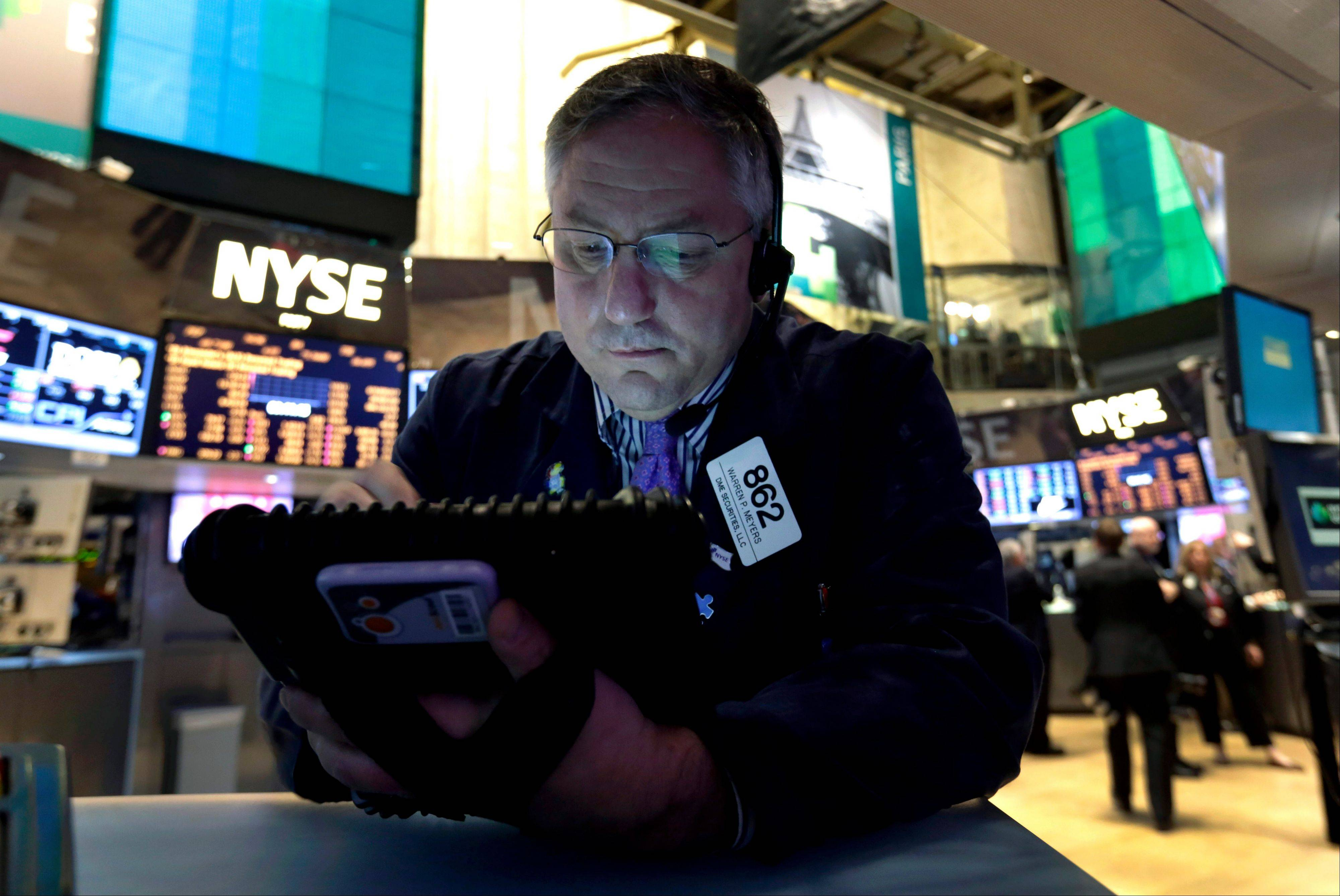 In this New York Stock Exchange Friday, Dec. 21, 2012, photo, Trader Warren Meyers uses his handheld device as he works on the floor of the New York Stock Exchange. Stocks are down Monday, Dec. 24, 2012, amid concern that lawmakers will fail to reach a deal to stop the U.S. going over the so-called fiscal cliff.