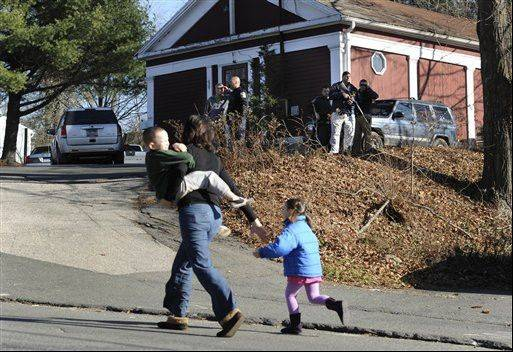 A mother runs with her children as police above canvass homes in the area following the shooting at the Sandy Hook Elementary School in Newtown, Conn. Experts say among the challenges will be spotting which children are struggling enough that they may need professional help.