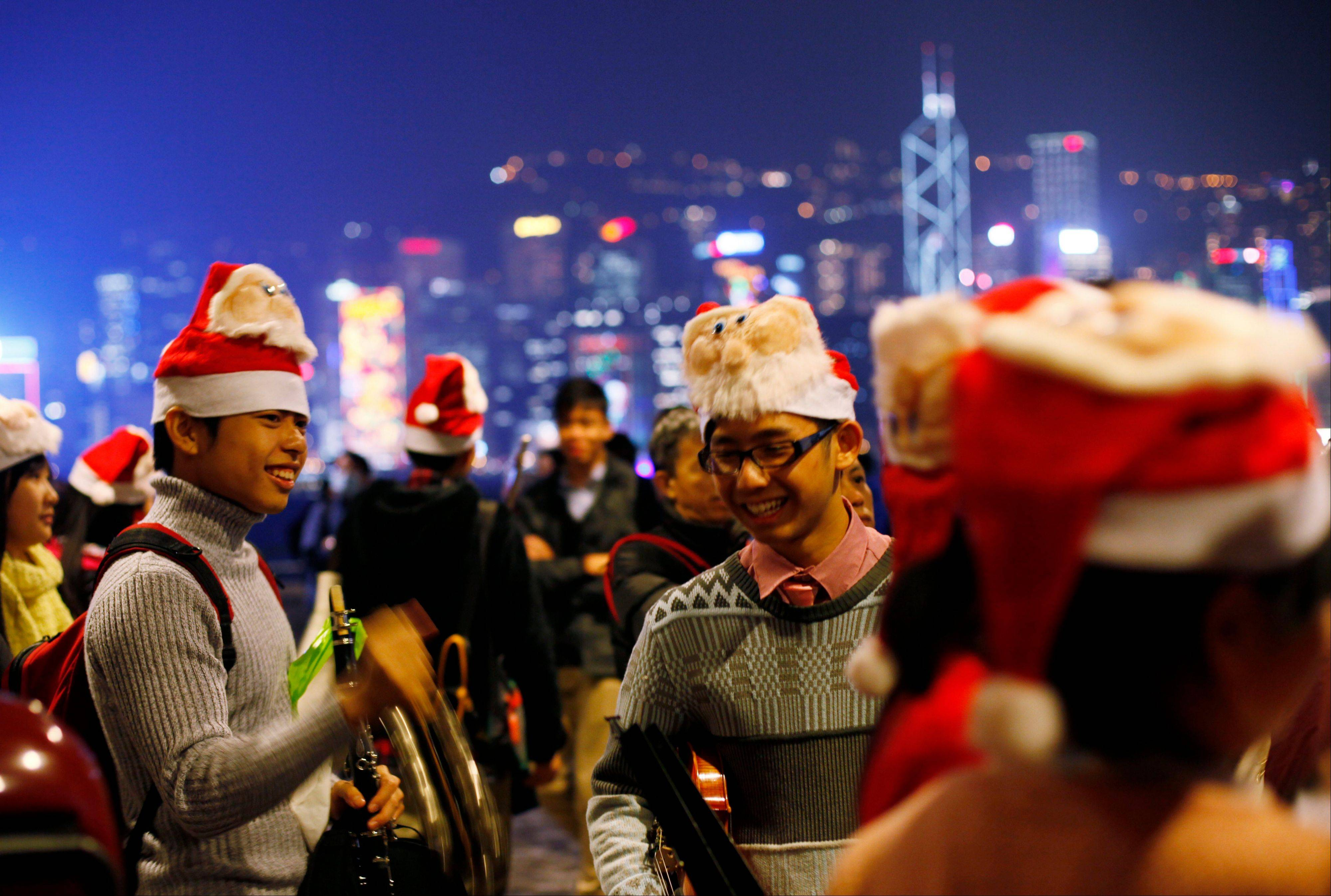 Students play Christmas songs during Christmas Eve along the shore of Victoria Harbour in Hong Kong Monday Dec. 24, 2012. Christmas is a public holiday and recognized as commercial event rather than religious event in Hong Kong.
