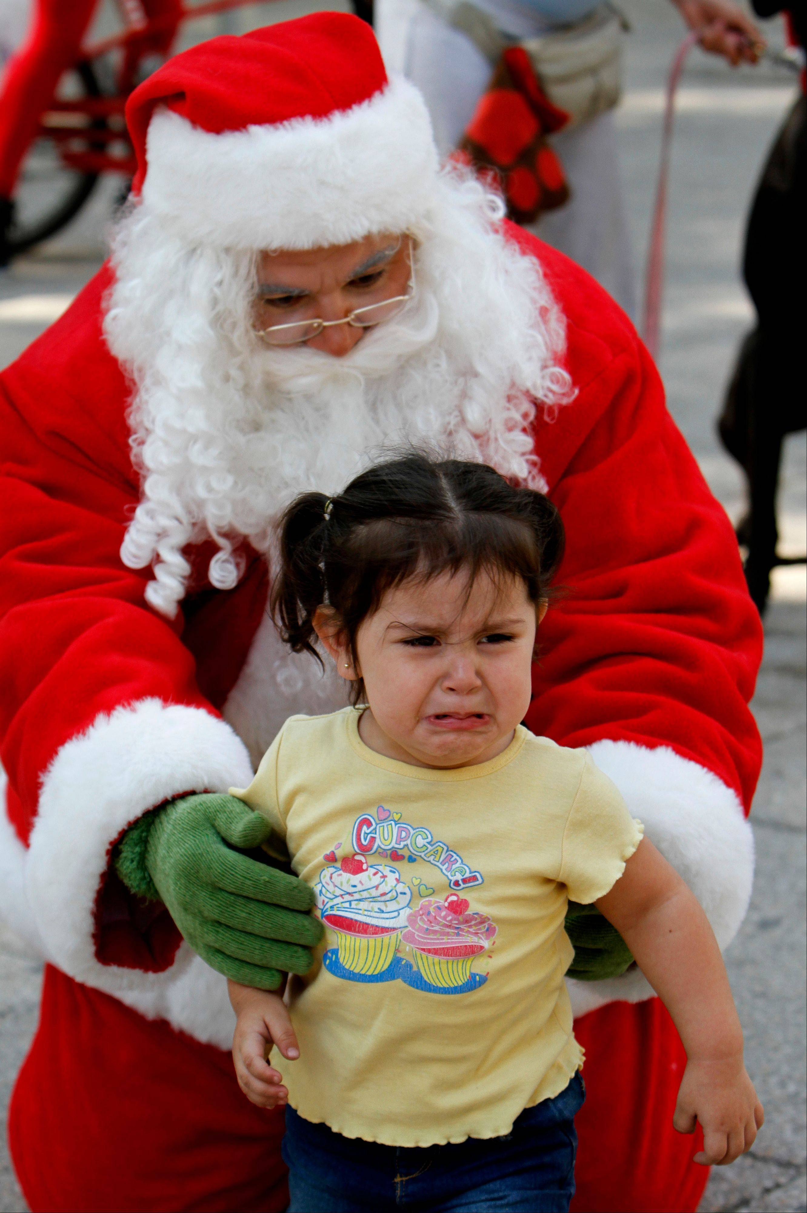 A girl cries as she poses for pictures with a man disguised as Santa Claus in Mexico City, Sunday, Dec. 23, 2012.