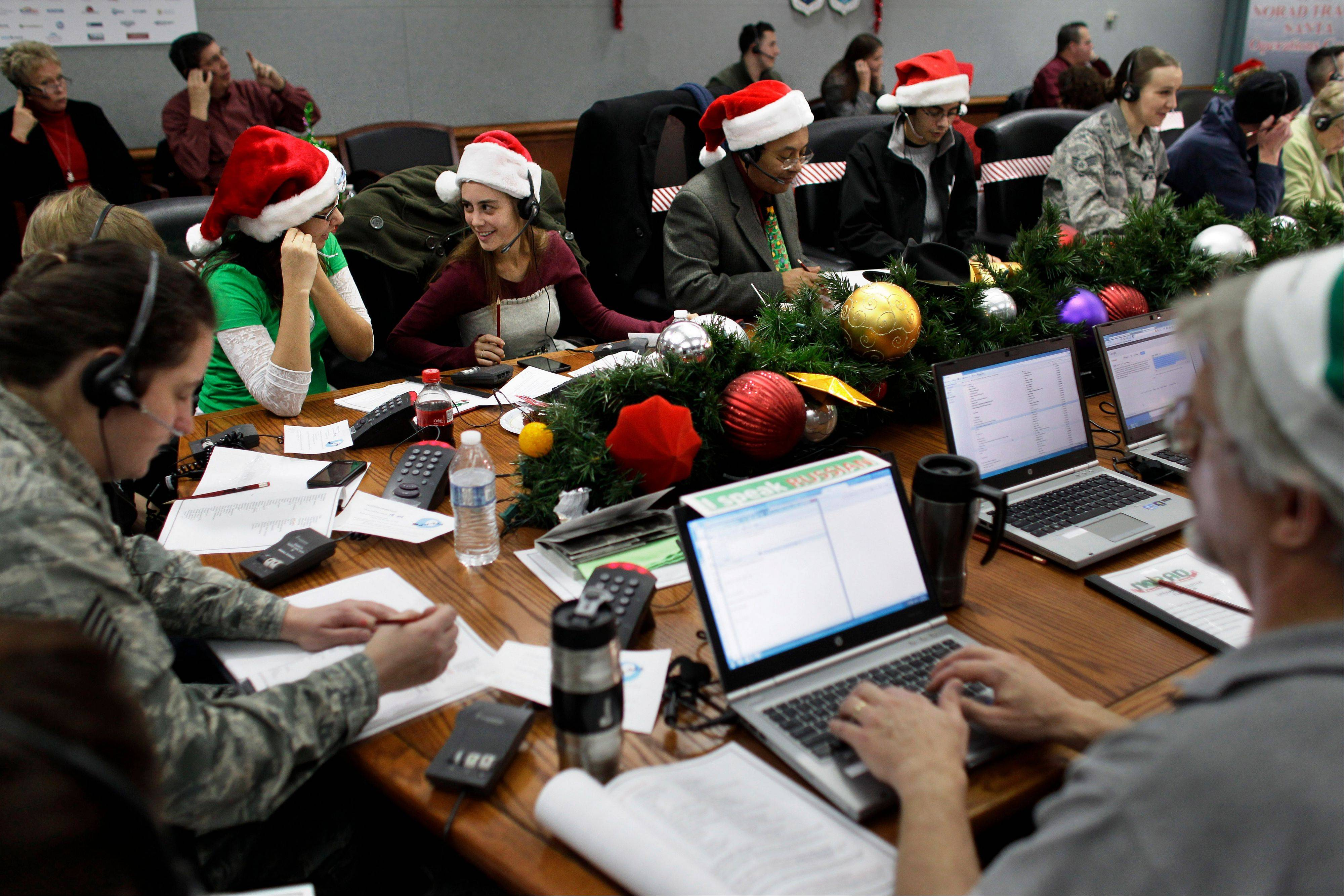Lizzie Solano, center, and her sister Sarah take phone calls from children asking where Santa is and when he will deliver presents to their house, during the fifth annual NORAD Tracks Santa Operation, at the North American Aerospace Defense Command, or NORAD, at Peterson Air Force Base, in Colorado Springs, Colo., Monday Dec. 24, 2012. Over a thousand volunteers at NORAD handle more than 100,000 thousand phone calls from children around the world every Christmas Eve, when NORAD continually projects Santa Claus's supposed progress delivering presents.