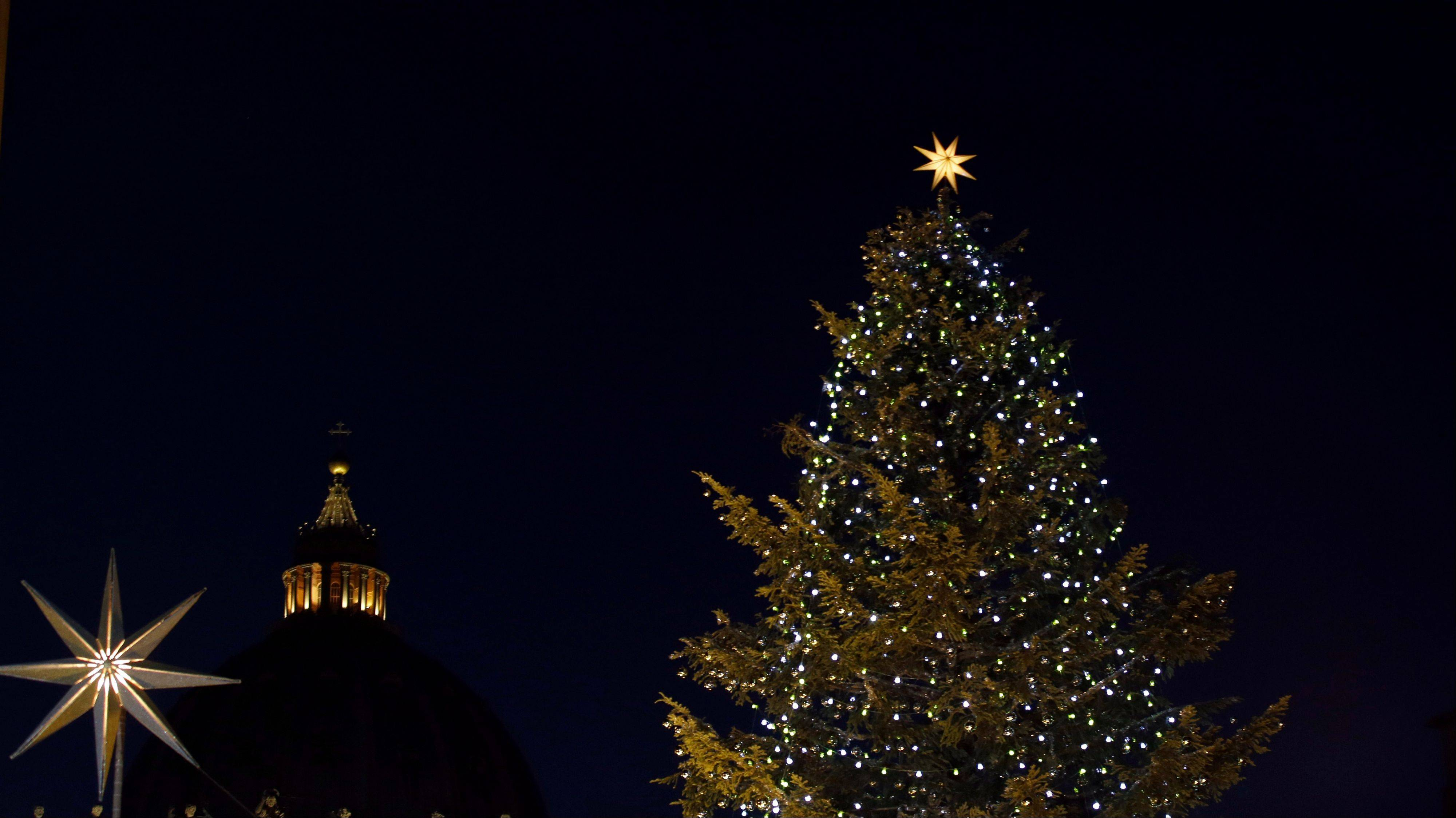 The dome of St. Peter's Basilica, center, is framed by a Christmas tree at the Vatican Monday, Dec. 24, 2012. Pope Benedict XVI has lit a Christmas peace candle set on the windowsill of his private studio overlooking square. Pilgrims, tourists and Romans gathered below in St. Peter's Square for the inauguration Monday evening of a Nativity scene and cheered when the flame was lit. Later, he will appear in St. Peter's Basilica to lead Christmas Eve Mass.