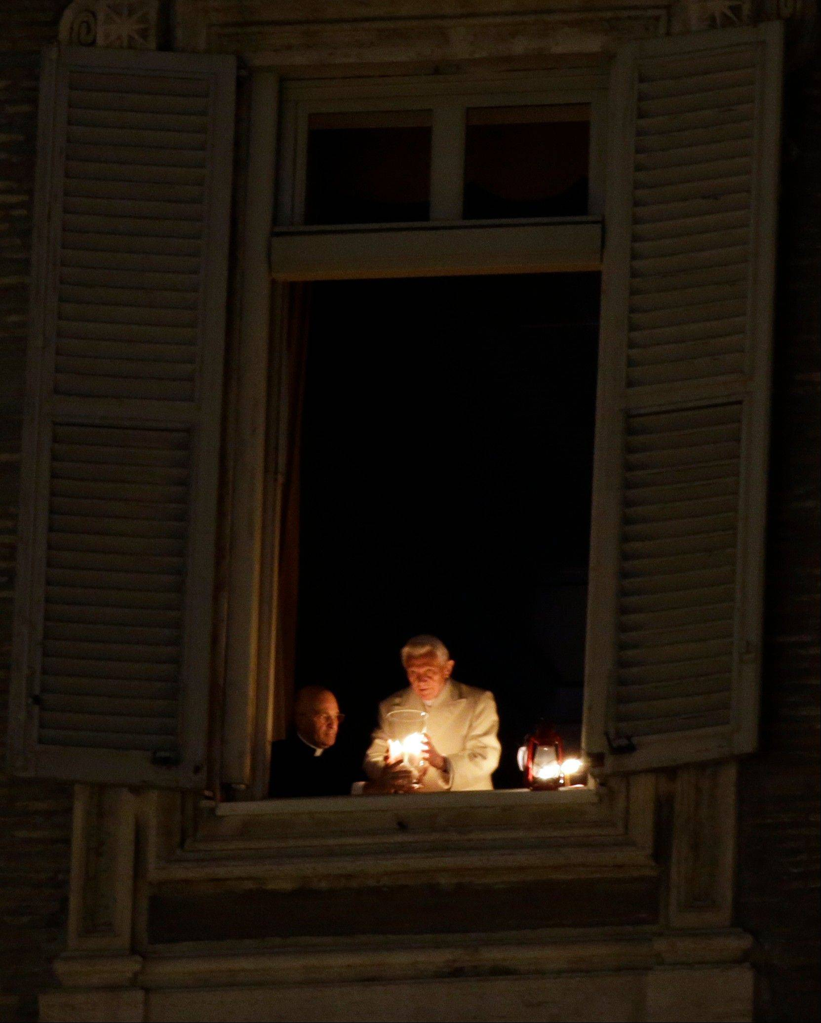 Pope Benedict XVI lights a candle at his studio window overlooking St. Peter's Square at the Vatican, after the unveiling of the Nativity scene, Monday, Dec. 24, 2012. Pope Benedict XVI has lit a Christmas peace candle set on the windowsill of his private studio overlooking square. Pilgrims, tourists and Romans gathered below in St. Peter's Square for the inauguration Monday evening of a Nativity scene and cheered when the flame was lit. Later, he will appear in St. Peter's Basilica to lead Christmas Eve Mass.