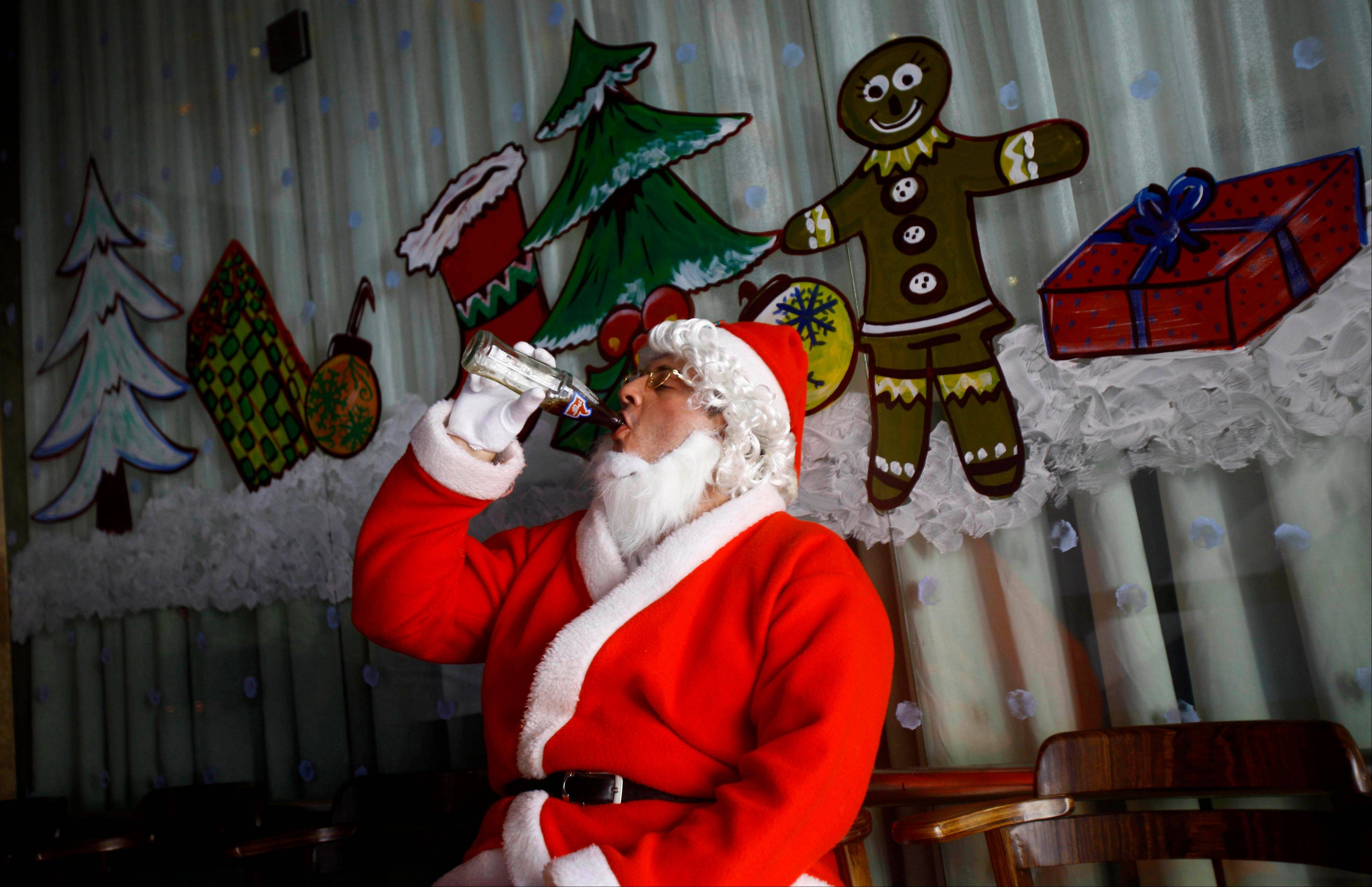 A man dressed as Santa drinks cola as he waits to take part in a Christmas celebration in Mumbai, India, Monday, Dec. 24, 2012. Although Christians comprise only two percent of the population Christmas is a national holiday and is observed across the country as an occasion to celebrate.