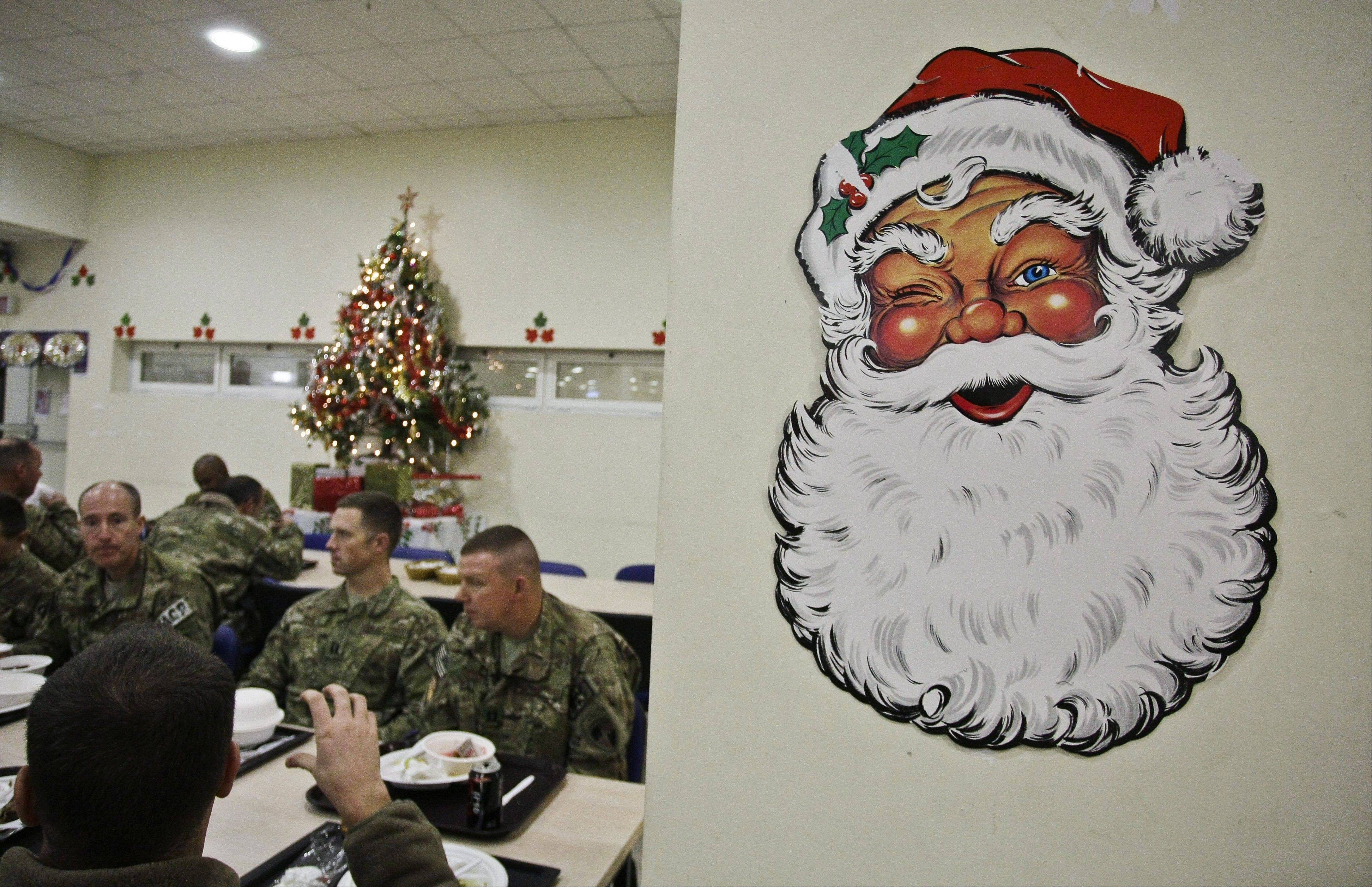 U.S. soldiers with the NATO- led International Security Assistance Force (ISAF) speak after eating dinner at a dinning hall on Christmas Eve at the U.S.-led coalition base in Kabul, Afghanistan, Monday, Dec. 24, 2014.