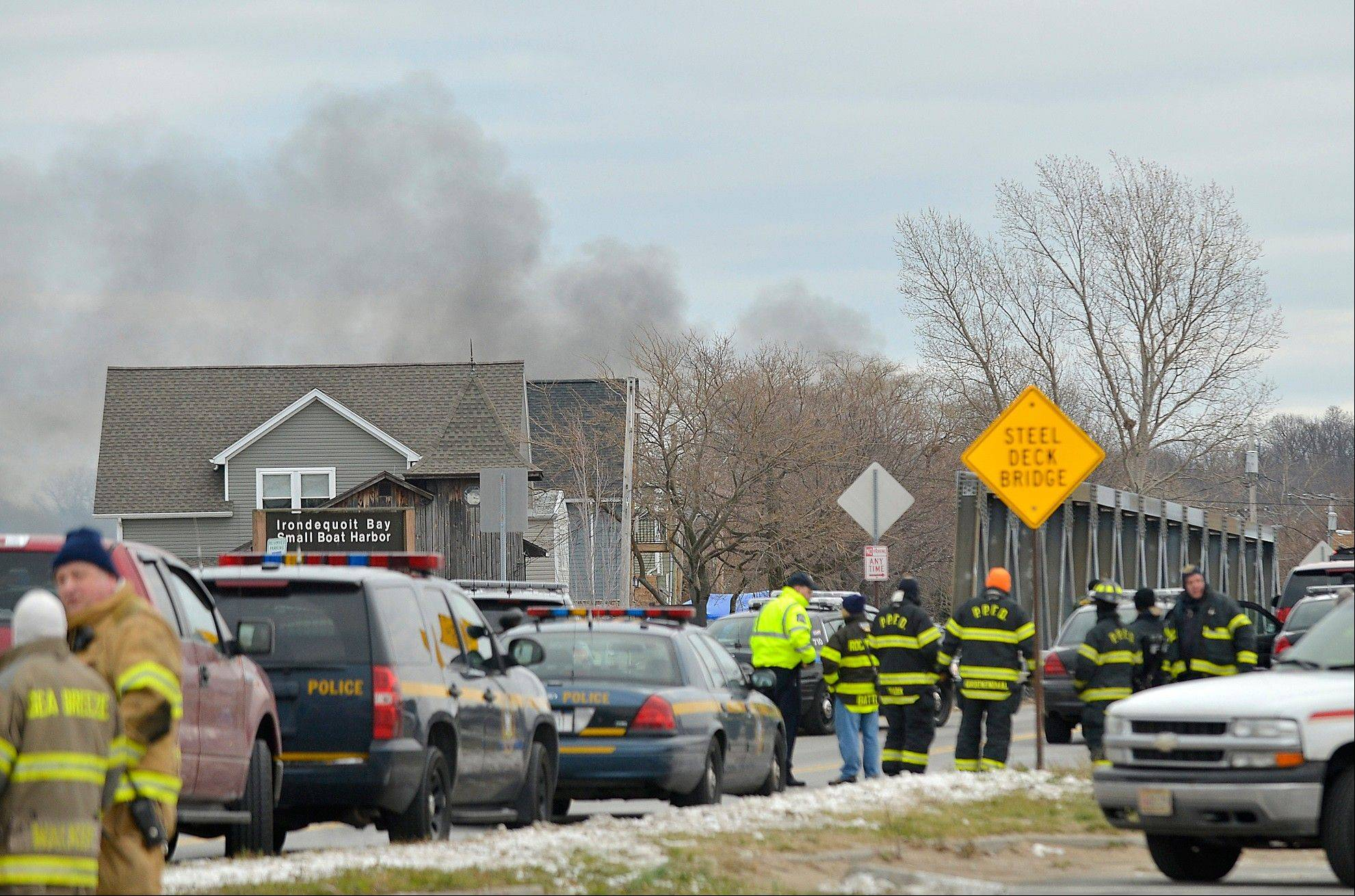 Smoke is seen from the site of a fire in Webster, N.Y., Monday, Dec. 24, 2012. Police in New York state say a man who killed two firefighters in a Christmas Eve ambush had served 17 years for manslaughter in the death of his grandmother.
