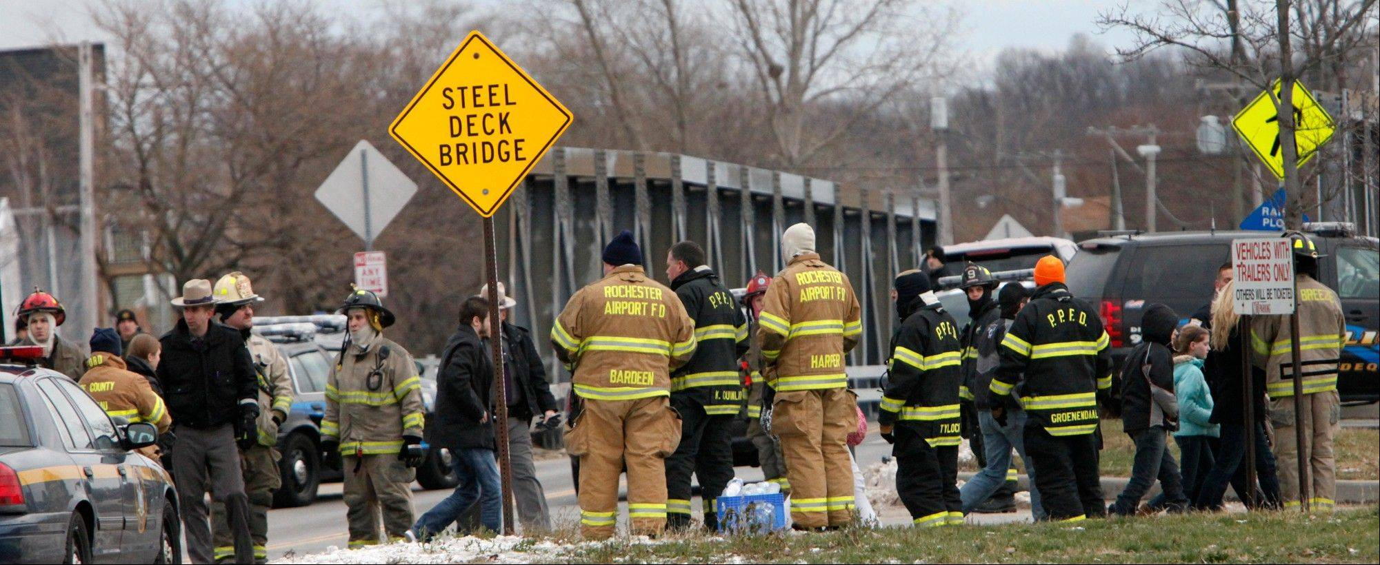 Residents are evacuated from the neighborhood, Monday, Dec. 24, 2012 in Webster, New York. A former convict set a house and car ablaze in his lakeside New York state neighborhood to lure firefighters then opened fire on them, killing two and engaging police in a shootout before killing himself while several homes burned. Authorities used an armored vehicle to evacuate the area.