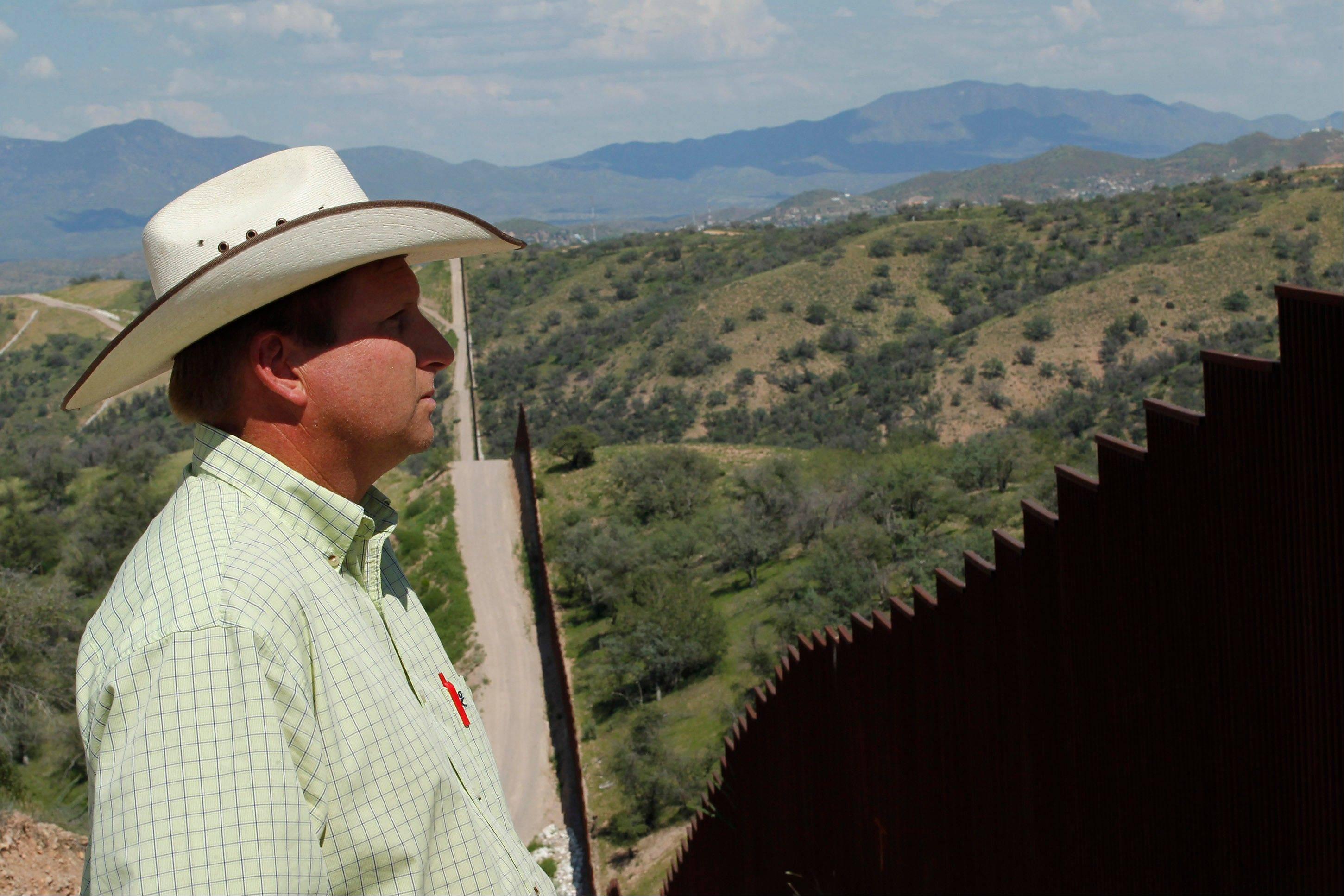 Rancher Dan Bell checks out part of the property he leases at the border fence between the United States and Mexico, in Nogales, Ariz. When Bell drives through the property, he speaks of the hurdles that the Border Patrol faces in his rolling green hills of oak and mesquite trees: The hours it takes to drive to some places, the wilderness areas that are generally off-limits to motorized vehicles, and the environmental reviews required to extend a dirt road.