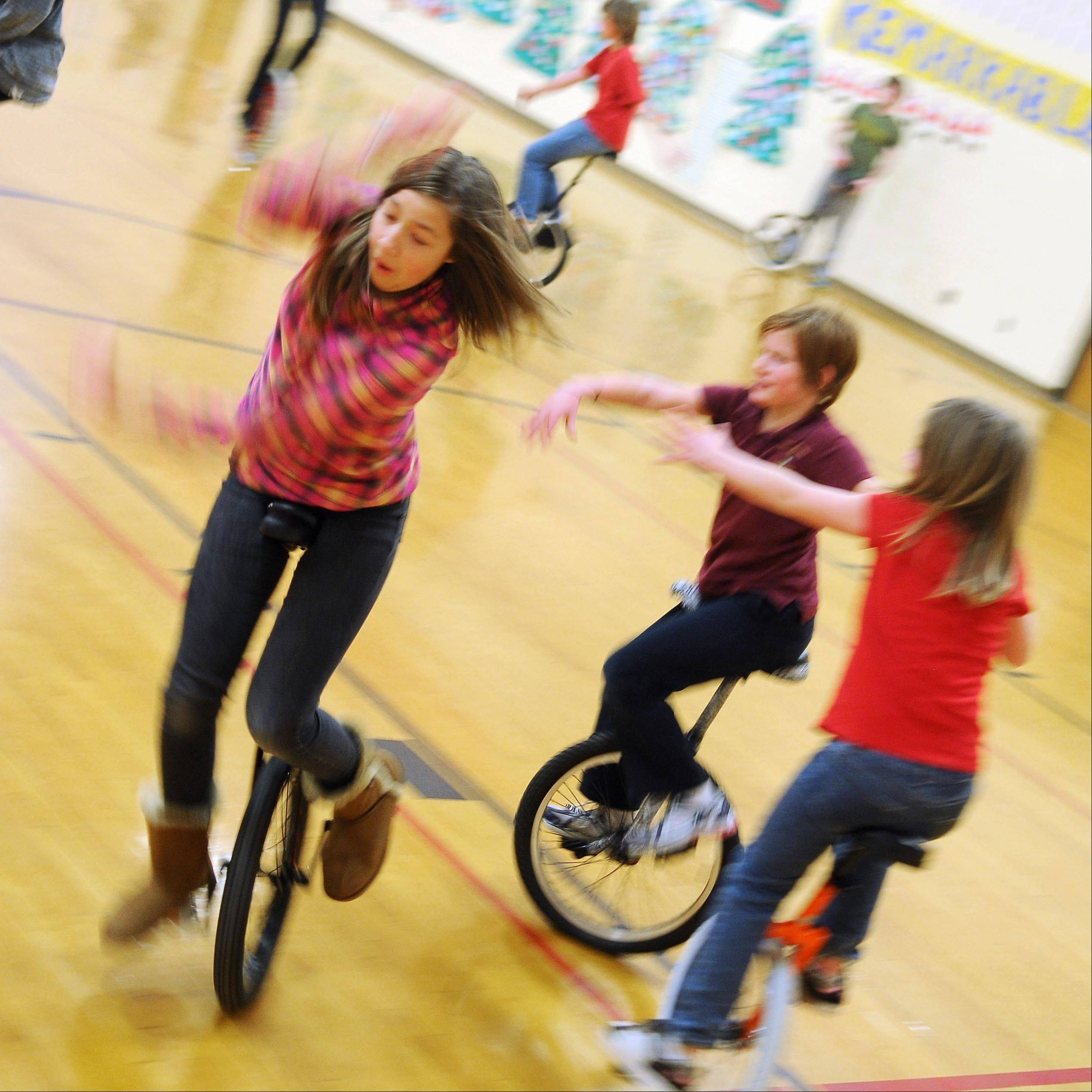 Mya Albright, twelve years-old, tries to avoid a tag in a game called 'Blob Tag' while riding a unicycle in the gymnasium at St. Croix Central Elementary School in Roberts, Wis. Mya participates in a community education program hosted by the St. Croix Central School district that welcomes young and old to learn and master the unicycle with the assistance of the Twin Cities Unicycle Club.