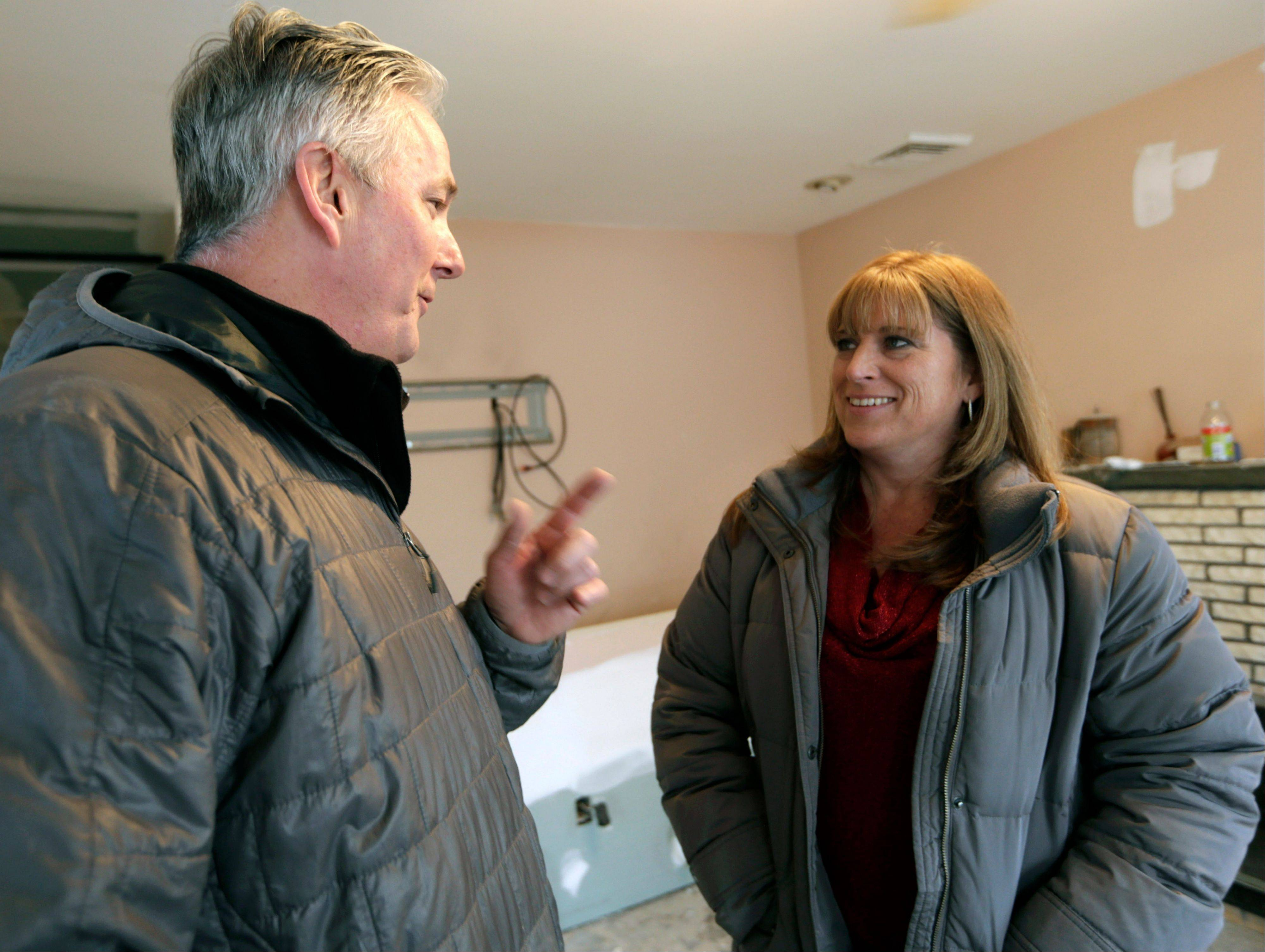 Donald Denihan, left, talks with Kerry Ann Troy during a visit to the Troy family house, under renovation after it was seriously damaged during Superstorm Sandy, in Long Beach, N.Y., Wednesday, Dec. 12, 2012. The Troys are living in a house in Point Lookout, N.Y., donated by strangers who found them. Denihan, who suffered several near-death experiences that convinced him his purpose in life was to help others, is paying for repairs. Denihan has instructed his workers to have the house ready by Christmas.