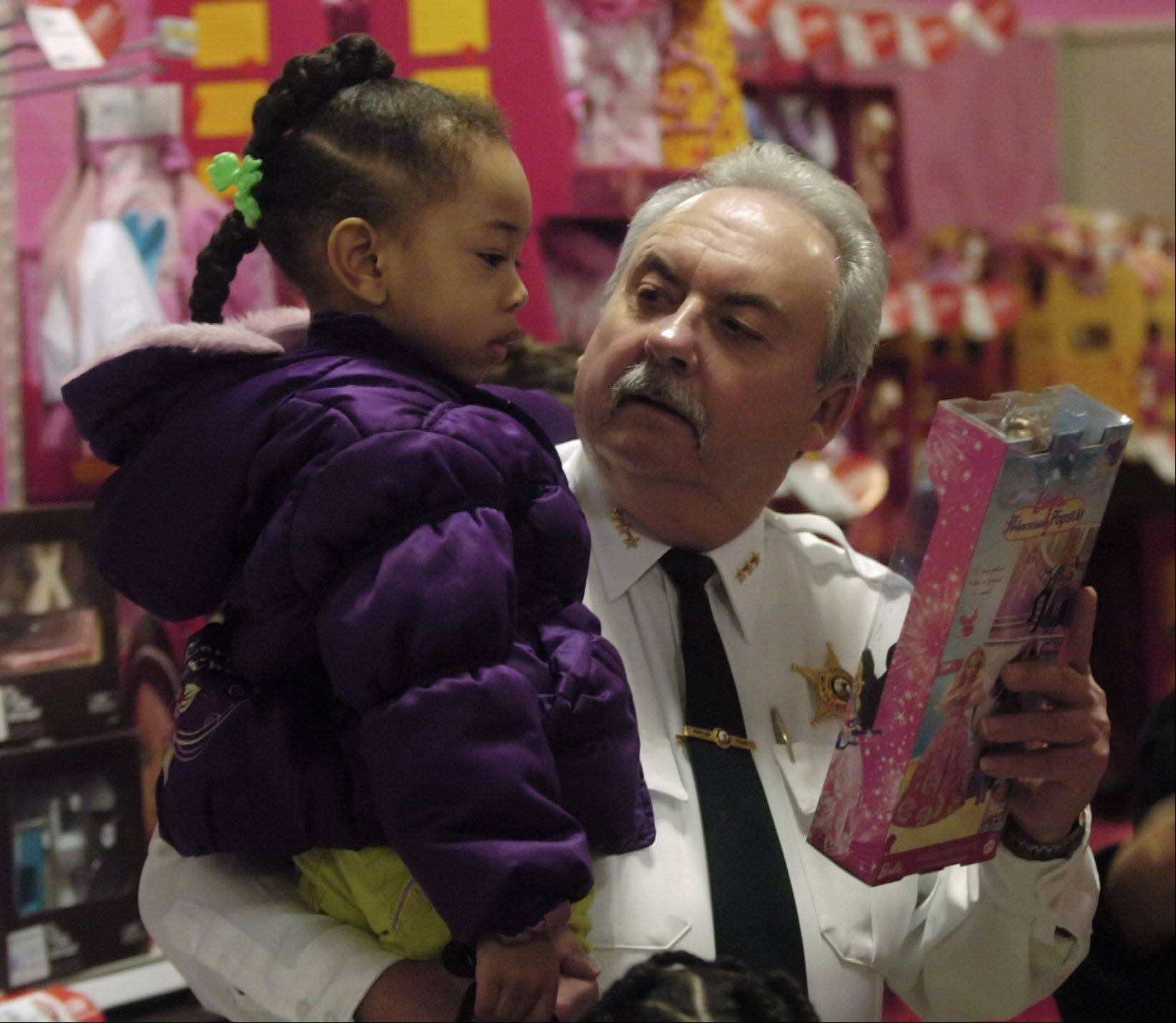 "Chief Ray Rose helps Aviyan Phillips, 4, of Mundelein pick out a Barbie during the Mundelein Police Department ""Shop with a Cop"" event at the Mundelein Super Target Saturday."