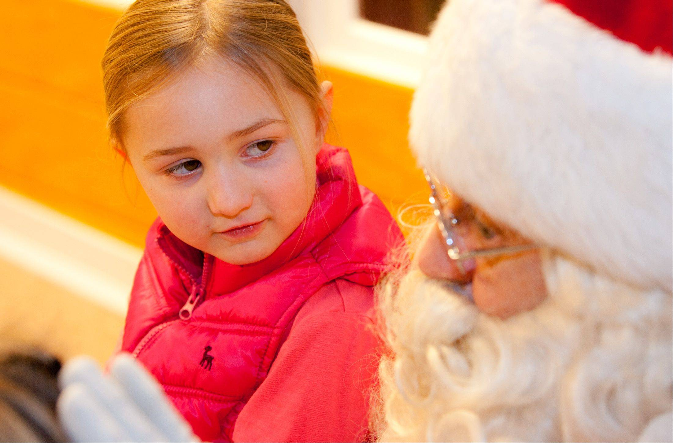 Lucy Rubenstein, 5, of Naperville, meets Santa at the Naperville Park District's Santa House, along the downtown Riverwalk.