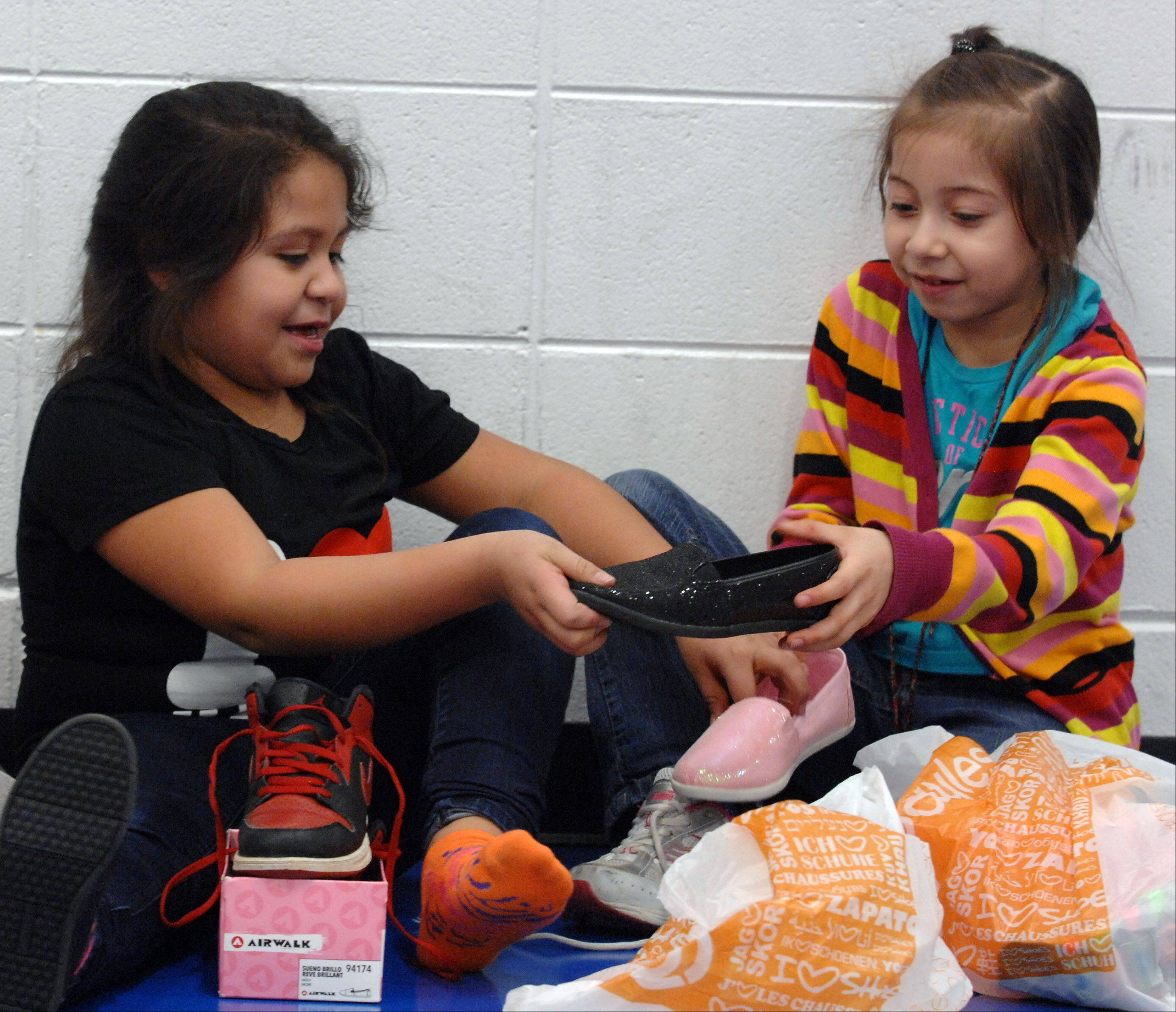 Perla Martinez, 6, left, and Daisy Silva, 6, check out each other's new shoes that they received from the Boys and Girls Club of Dundee Township at Golfview Elementary School in Carpentersville Thursday. Payless Shoes donated 1.2 million shoes around the country, including about 300 to this branch of the Boys and Girls Club, who then passed them out at two locations.
