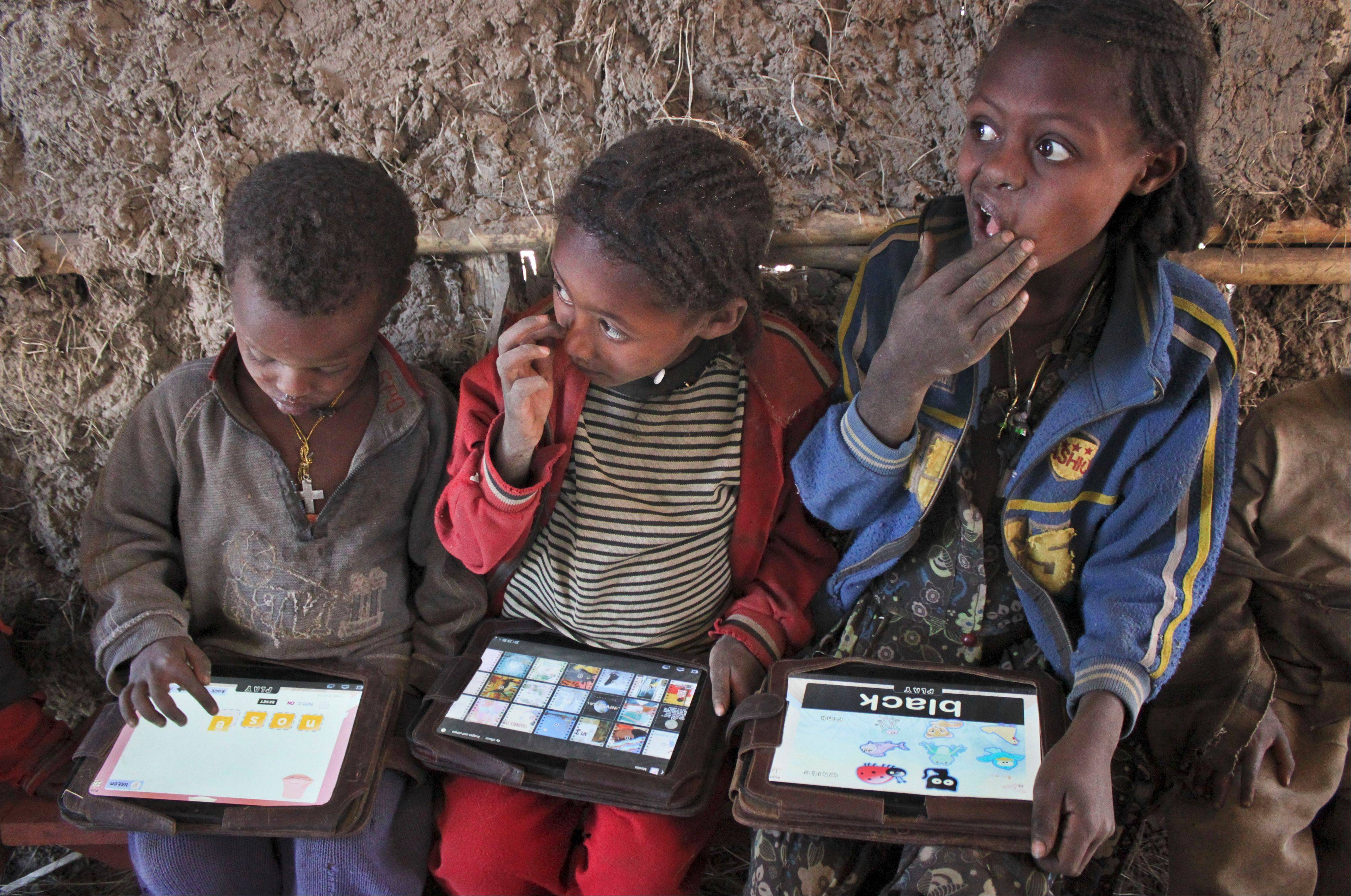 Children play with tablet computers given to them by the One Laptop Per Child project in the village of Wenchi, Ethiopia. The project gave tablets to the children in the poor, illiterate village to see how much the children could teach themselves and now many kids can recite the English alphabet and spell words in English